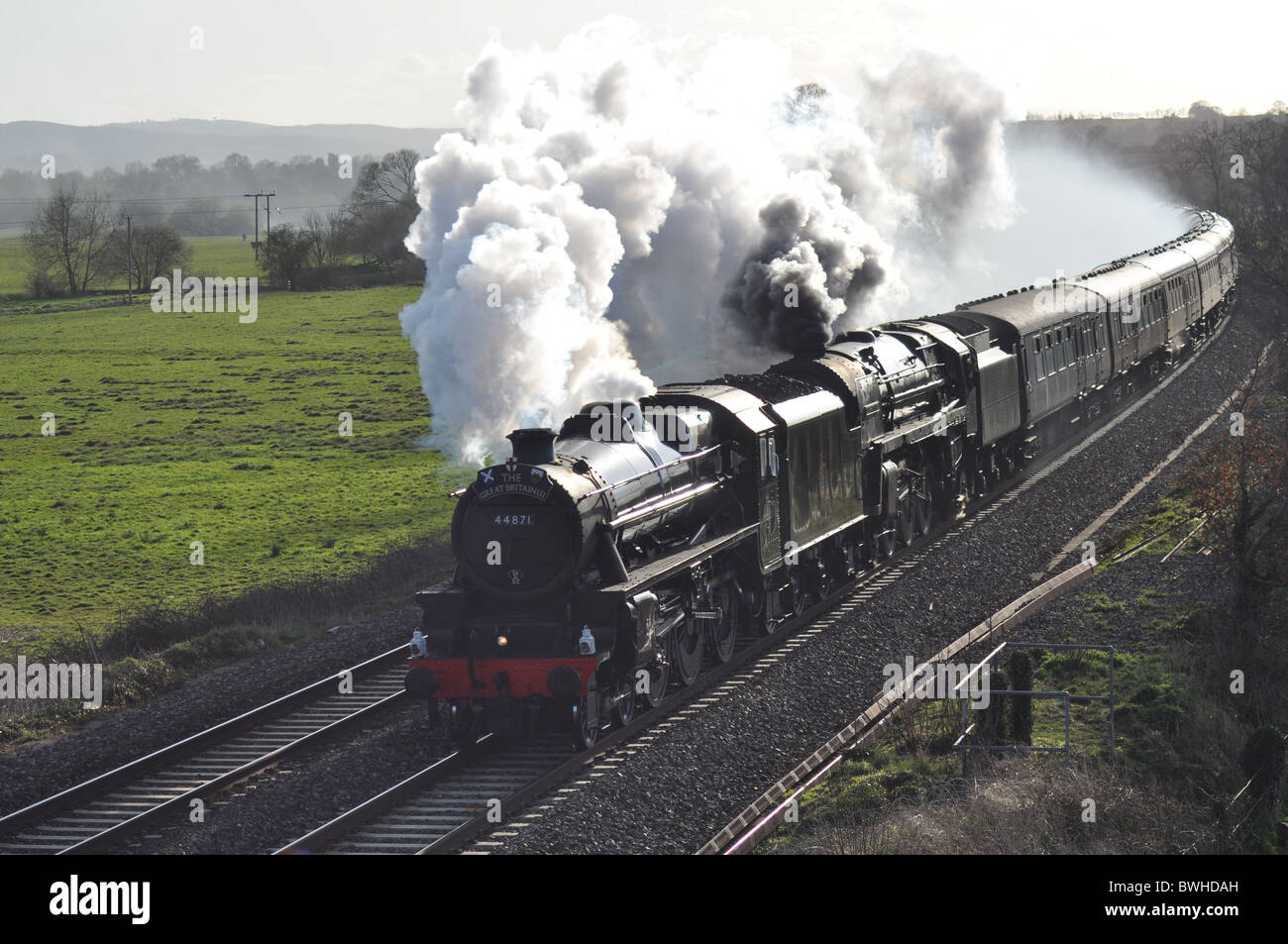 Double headed steam locomotives on a Railtour, in full steam, caught in the evening sunlight at Silverton, Nr Exeter, - Stock Image