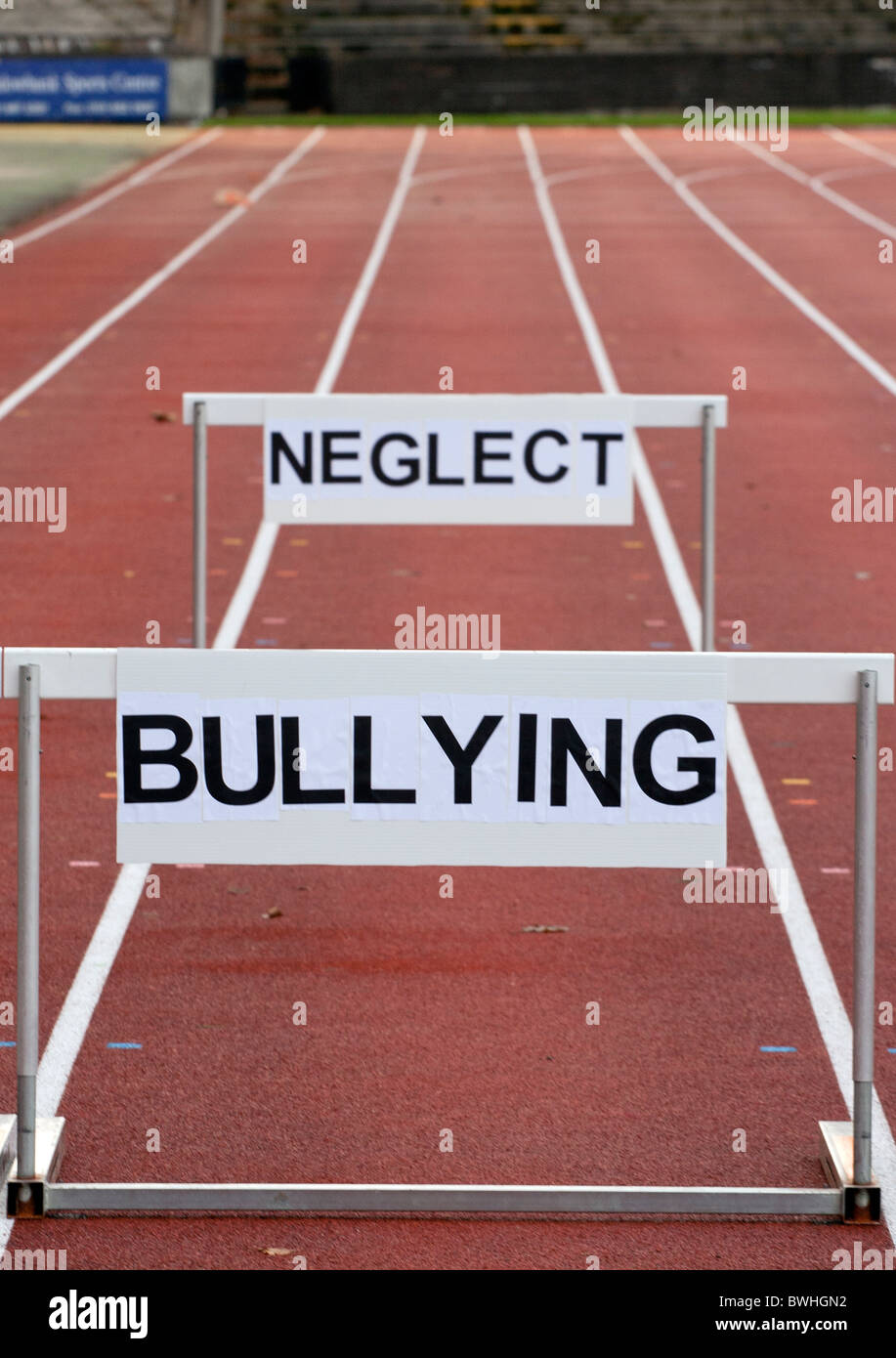 Hurdles on a track at Meadownbank Stadium with neglect and bullying depicted as life hurdles - Stock Image