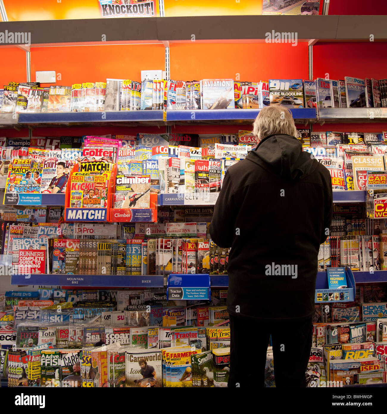 Rear view of a man browsing magazines in WH Smith newsagents UK - Stock Image