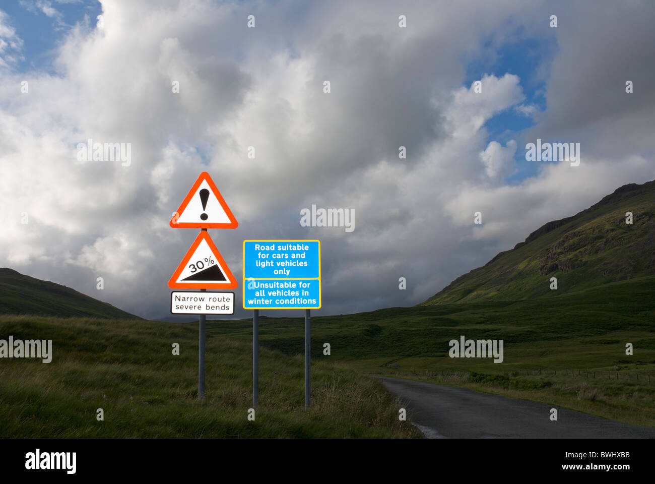 Road signs warning of steep roads and winter conditions, Hardknott and Wrynose Passes, Lake District, Cumbria, England - Stock Image