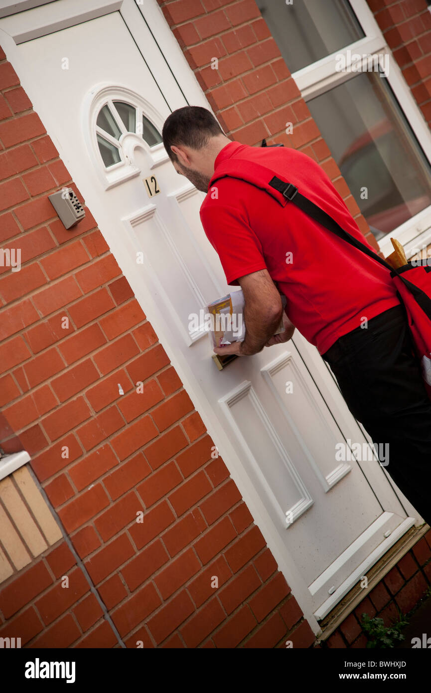 A Royal Mail postal worker delivering the mail, UK - Stock Image