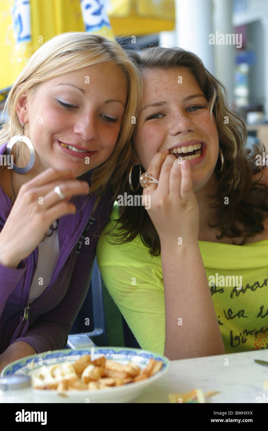 Two happy teenage girls eating french fries outside at luncheonette terrace from a plate with hands. - Stock Image