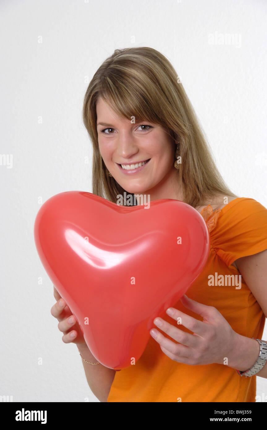 woman portrait laughing heart balloon balloon love symbol falling in love studio inside - Stock Image