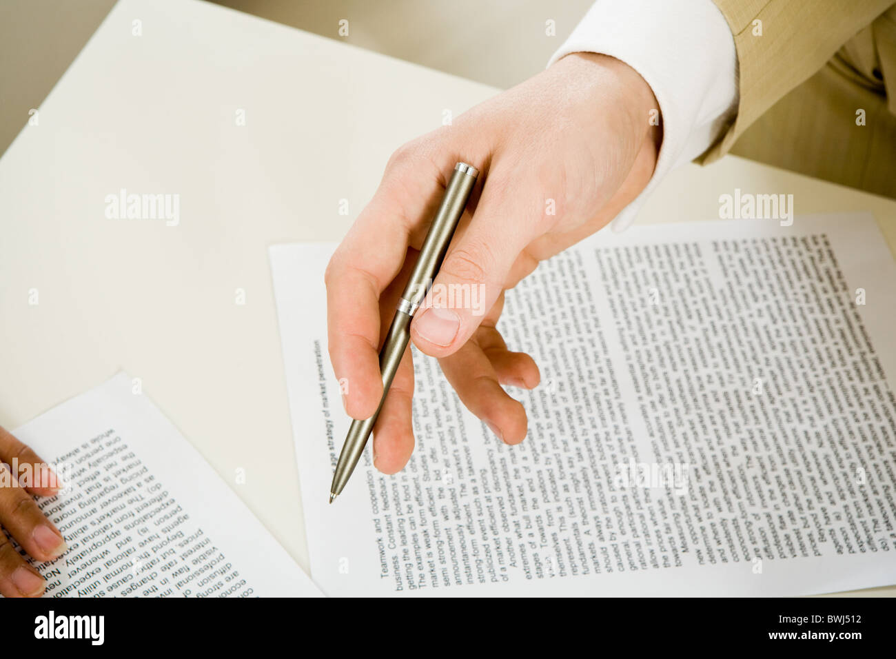 Image of male hand with ballpoint over paper during discussion of plans - Stock Image