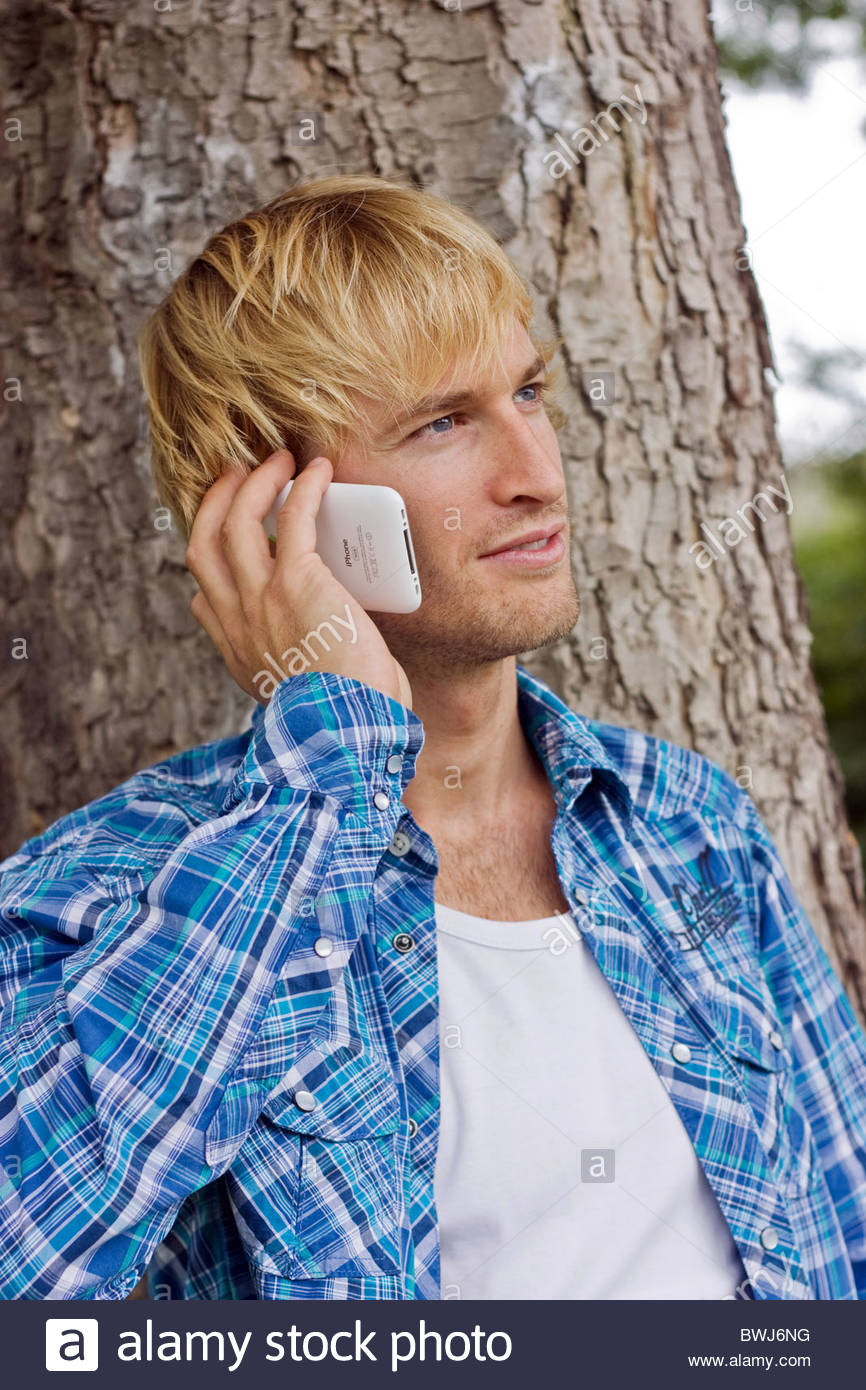 portrait of young blond man calling with mobile phone - Stock Image