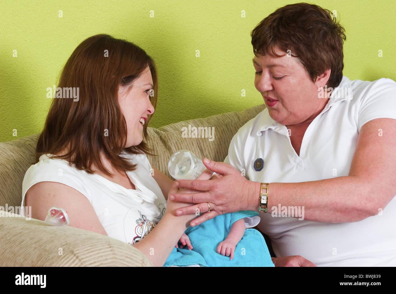 Maternity nurse helping mum bottle feeding new born baby - Stock Image