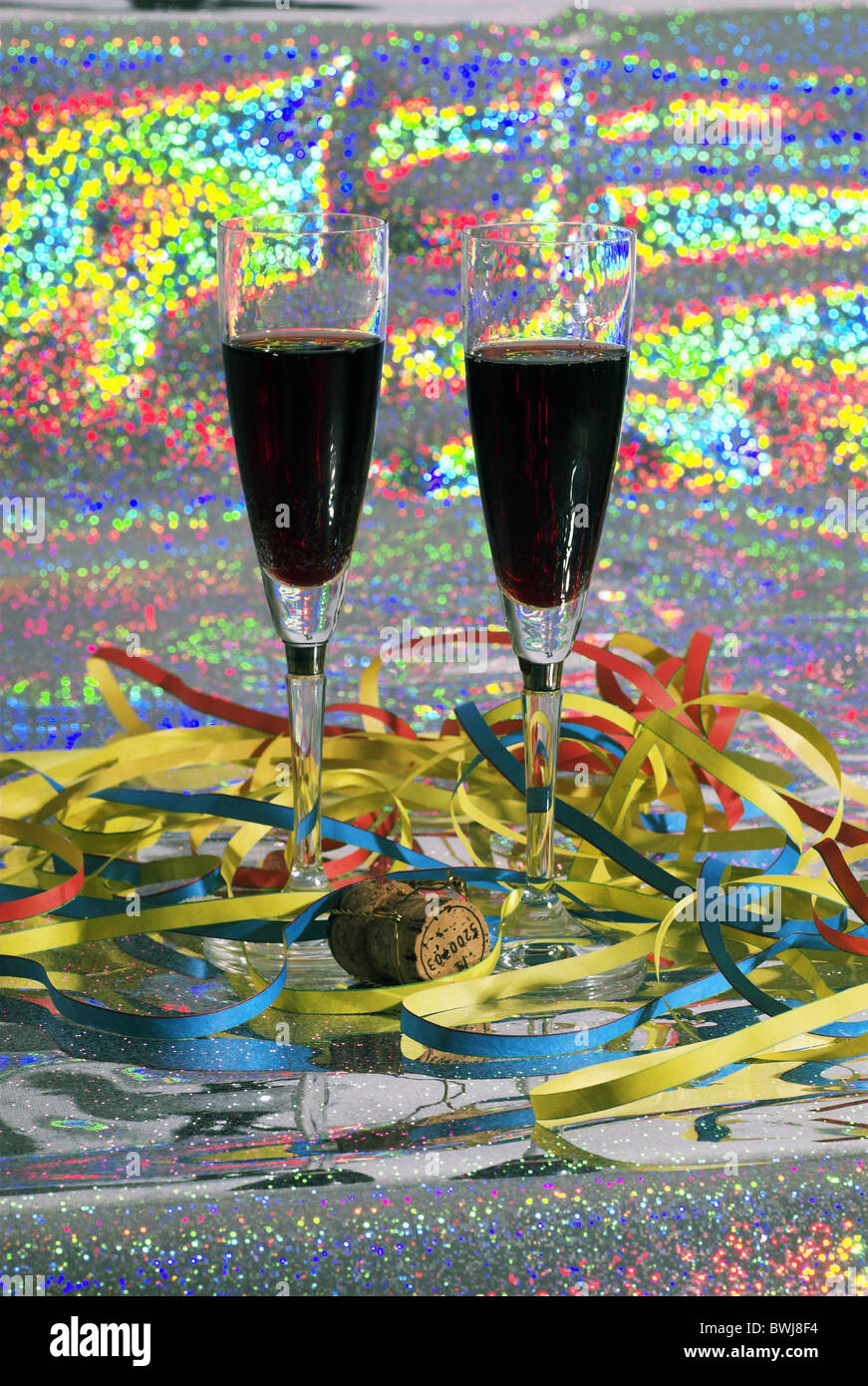 champagne glasses wine stumbling celebration celebrations streamers decoration adornment New Year Eve party - Stock Image