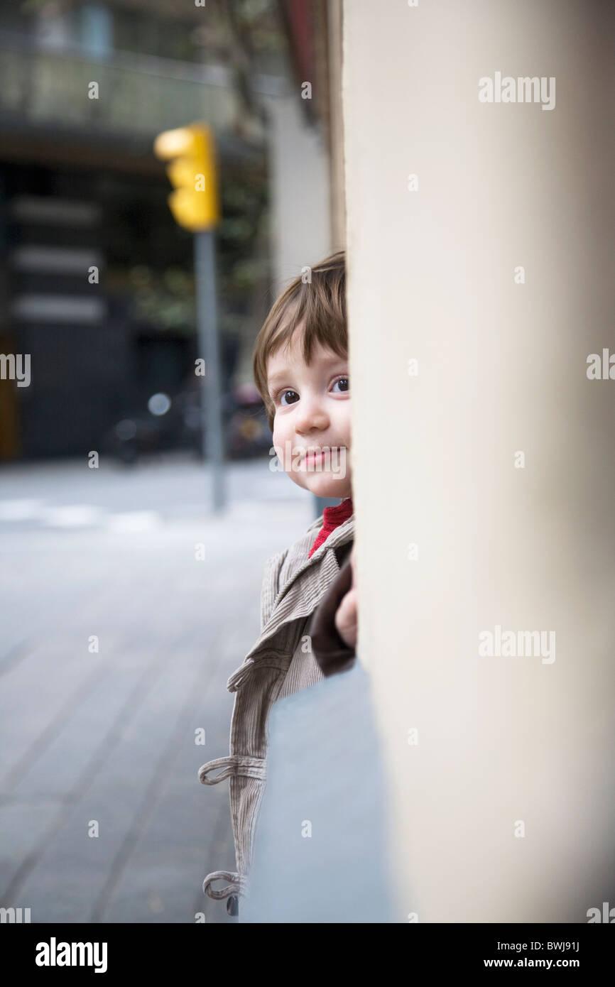 23 month old boy hiding in doorway - Stock Image