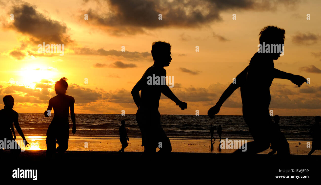 Silhouette of football players on the beach - Stock Image