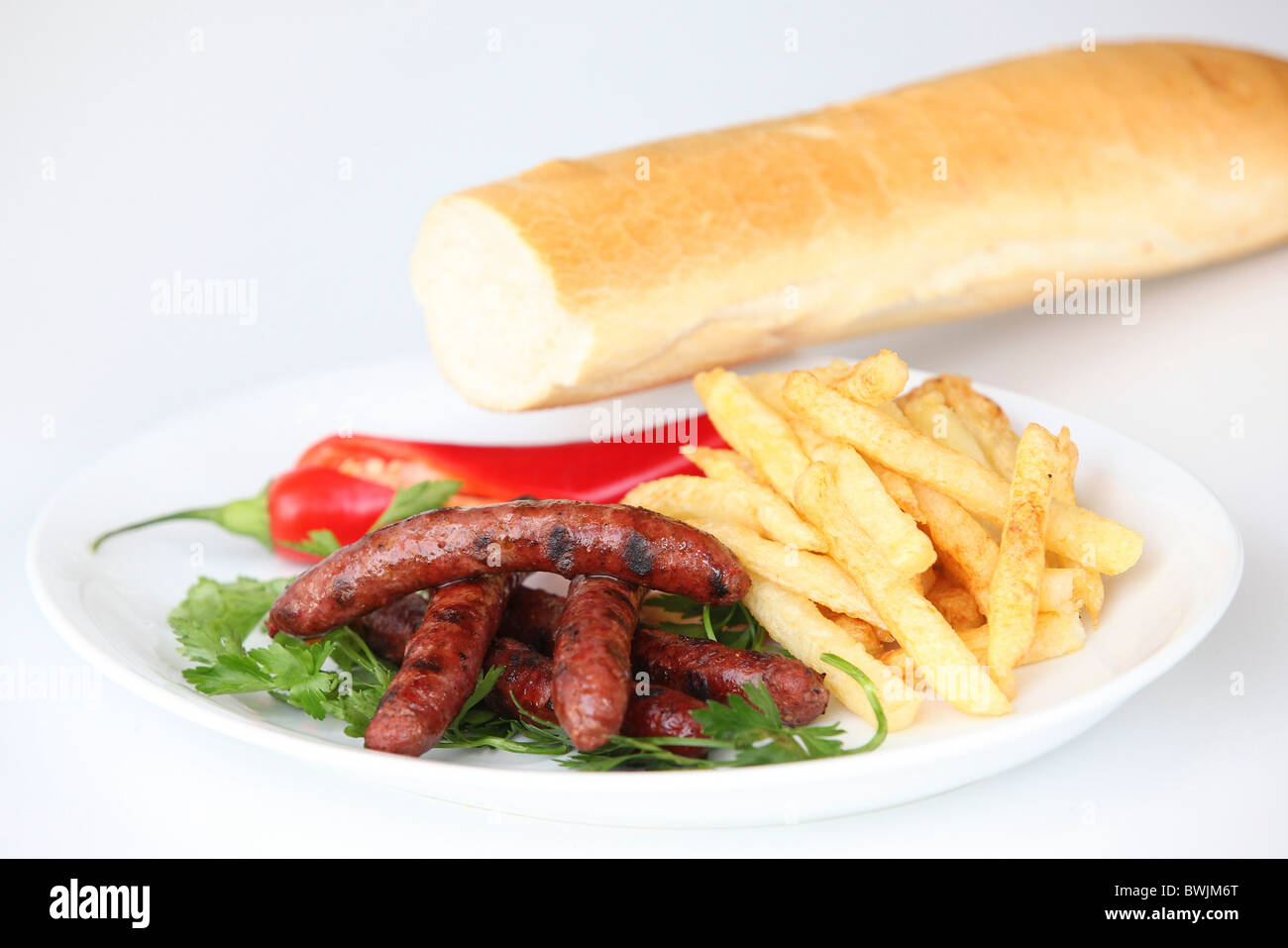 Char Grilled Merguez sausages with french fries - Stock Image