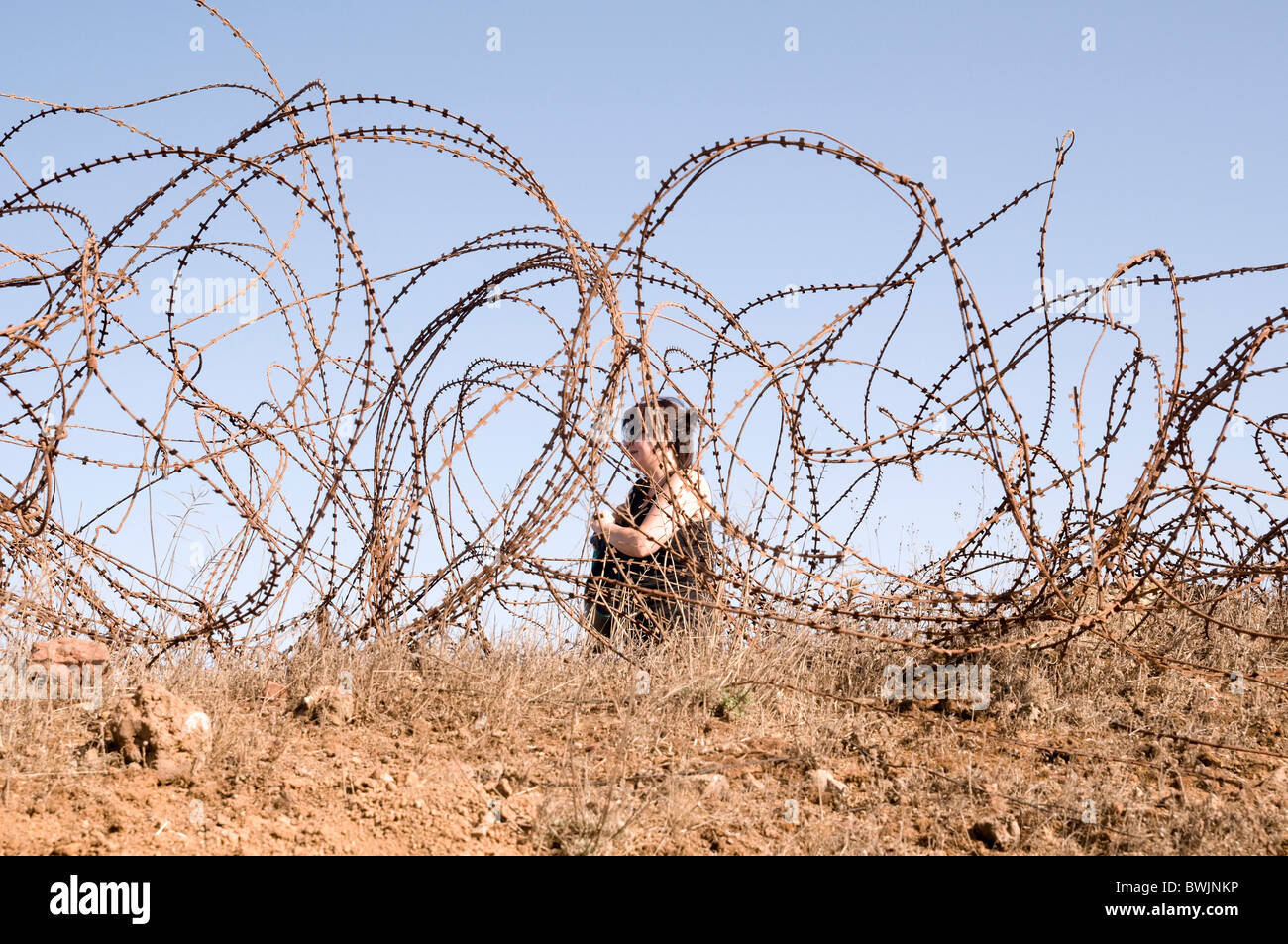 Woman, in her forties, confined by a Barbed wire fence - Stock Image