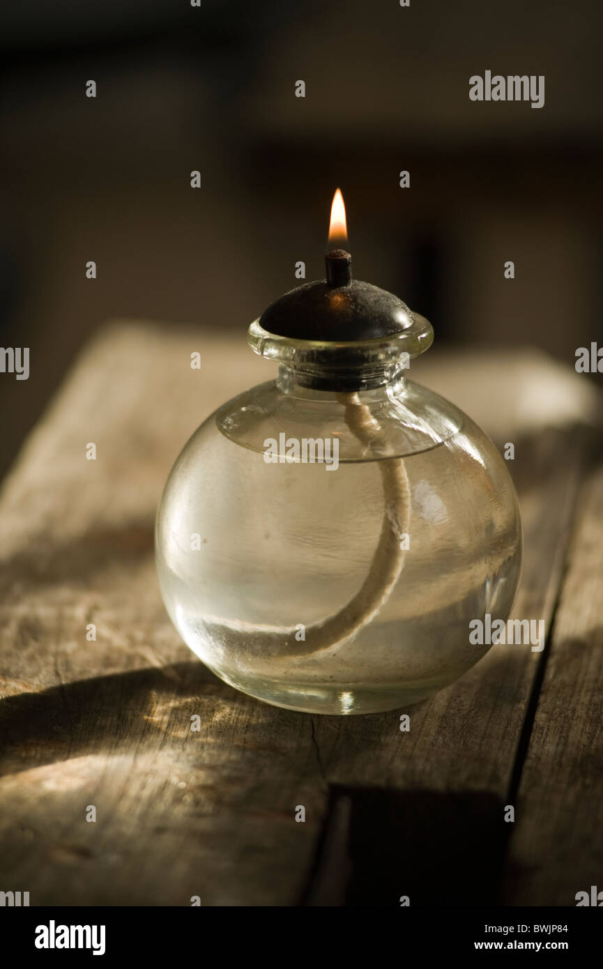 Oil lamp with flame alight on a rough wooden table with weak sunlight throwing long shadows. - Stock Image