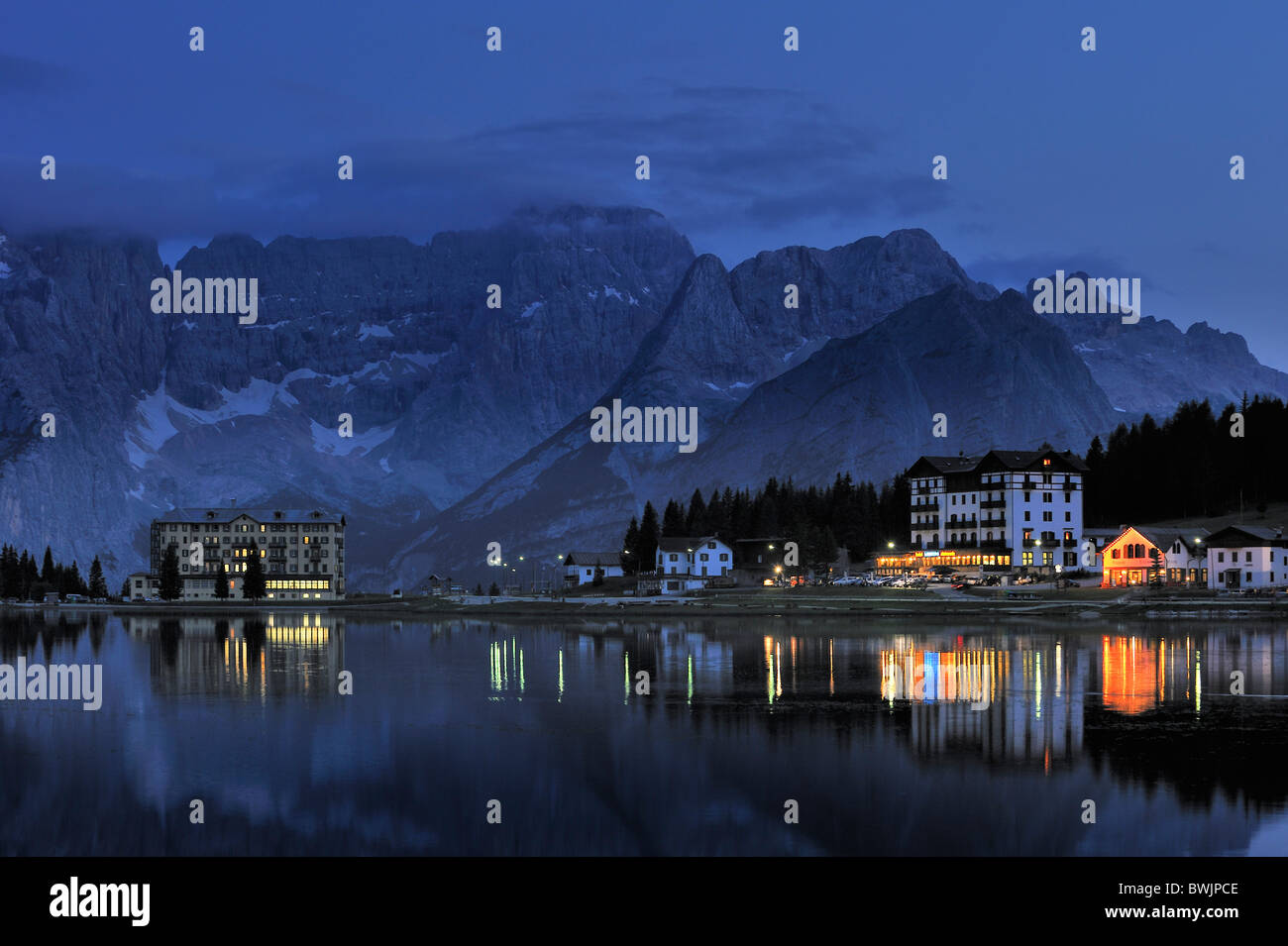The mountain range Gruppo del Sorapis and hotels at night along lake Lago di Misurina in Auronzo di Cadore, Dolomites, - Stock Image