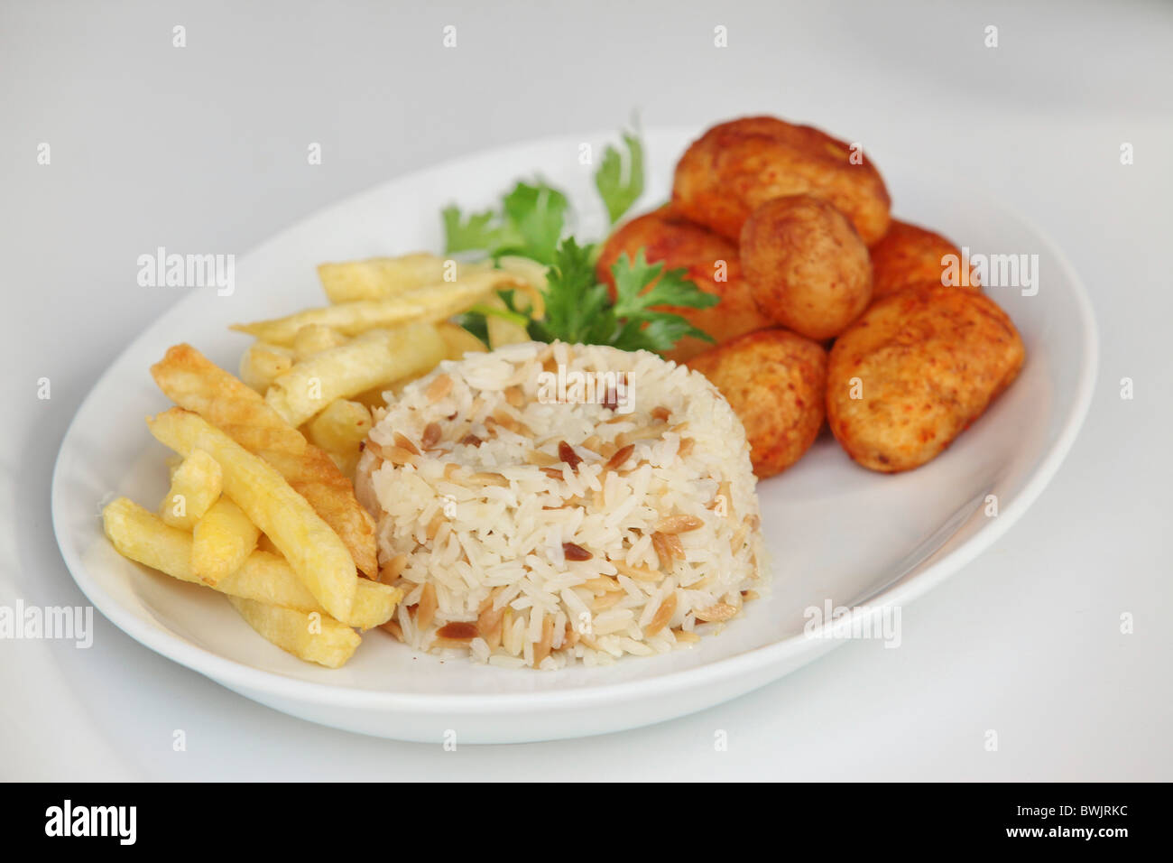 A plate of carbohydrates with baked potato rice and french fries - Stock Image