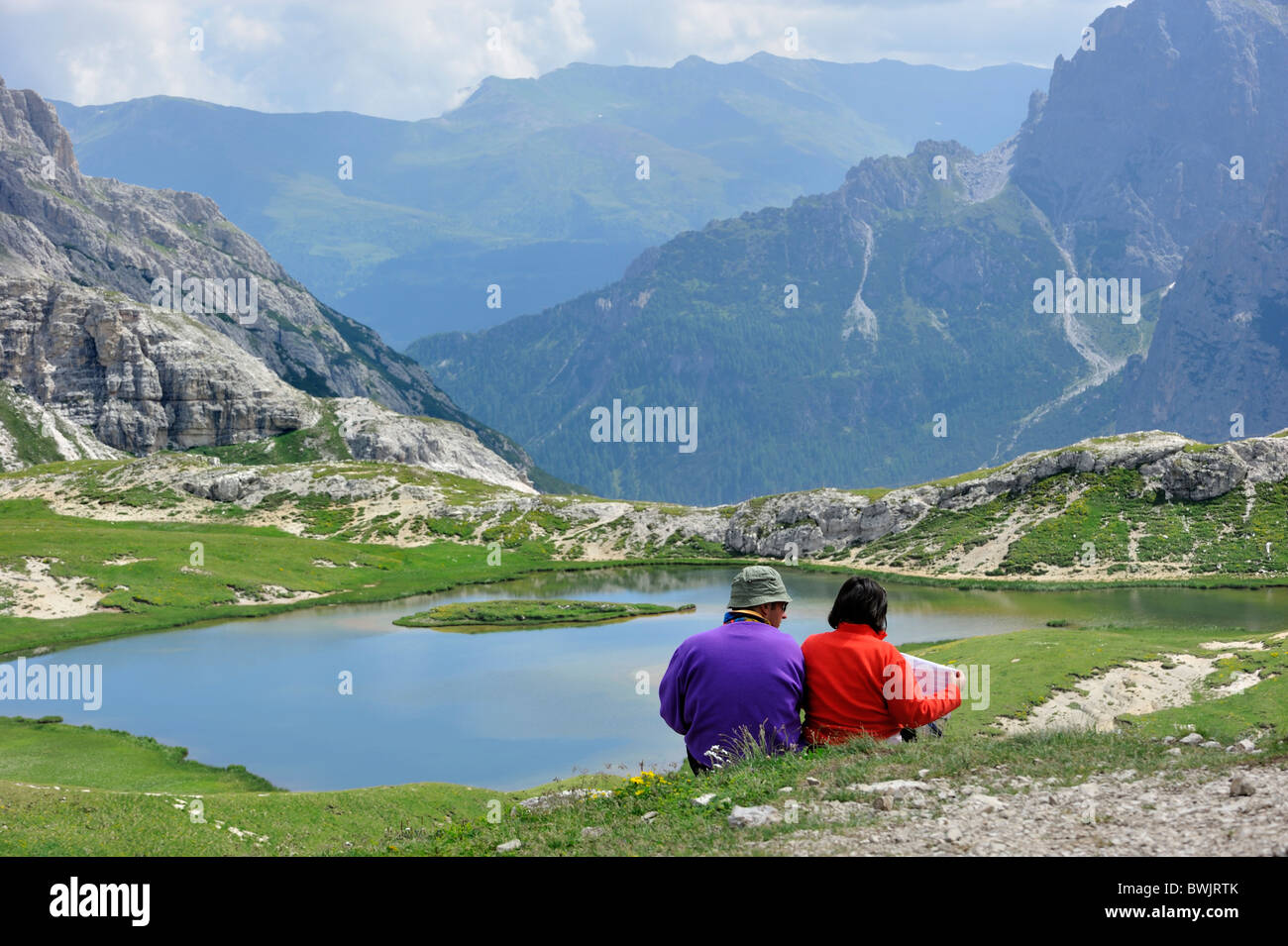 Couple mountain walkers reading map at lake in the Dolomites, Italy on