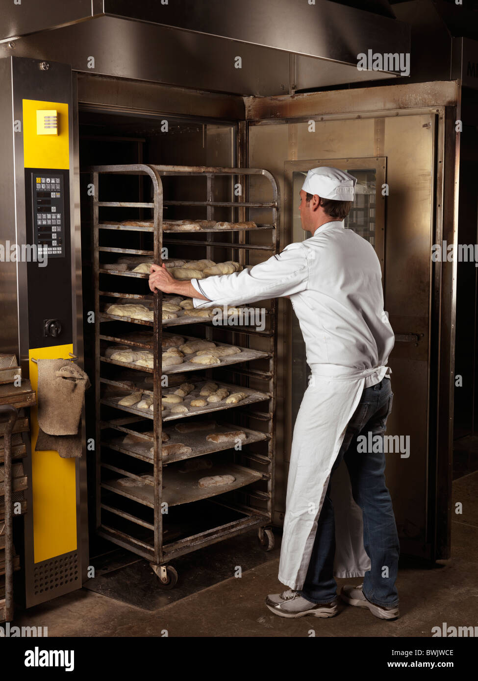 Baker rolling in a rack trolley with buns in a bakery oven - Stock Image