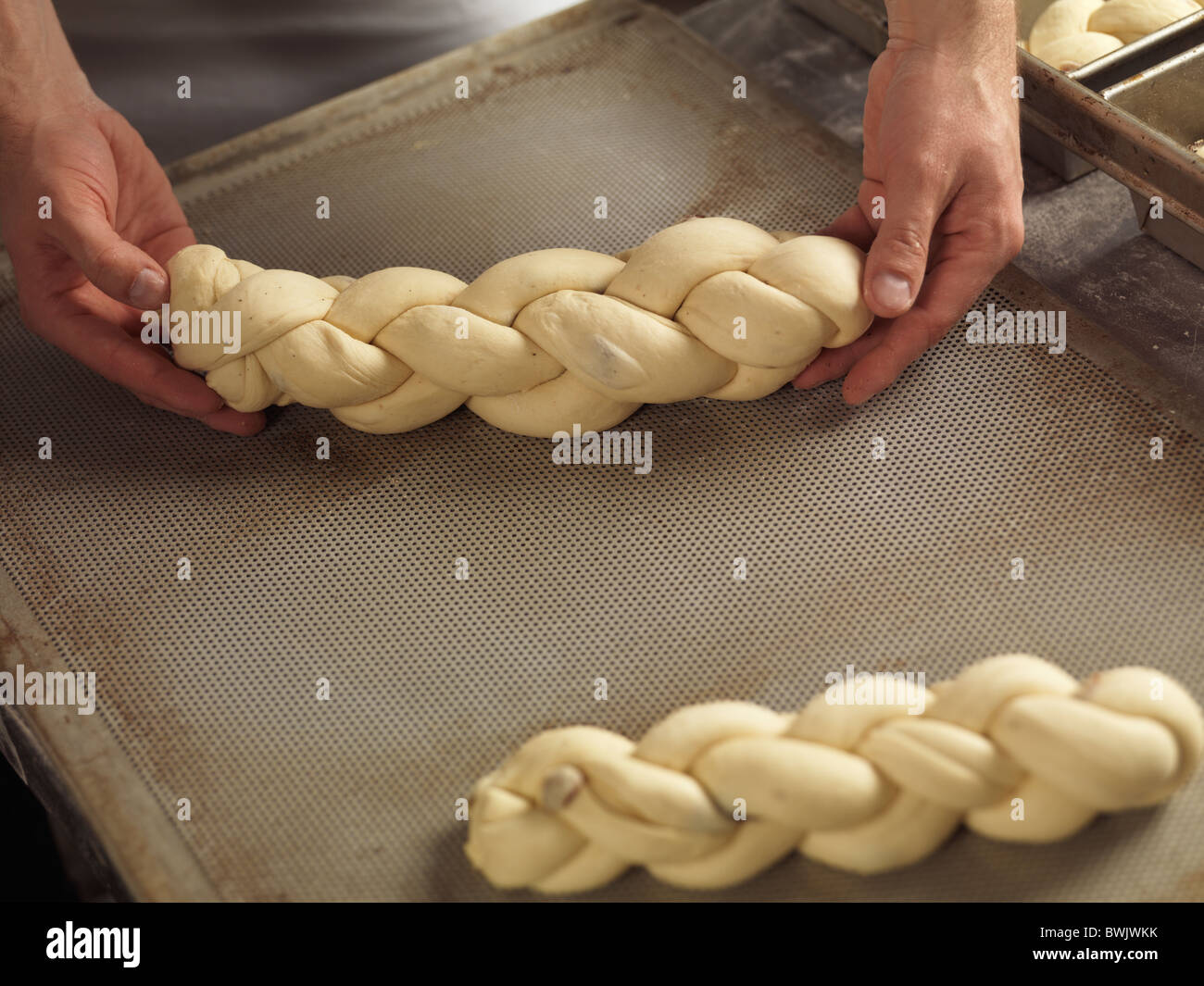 Closeup of bakers hands laying braided bread challah on a baking tray - Stock Image