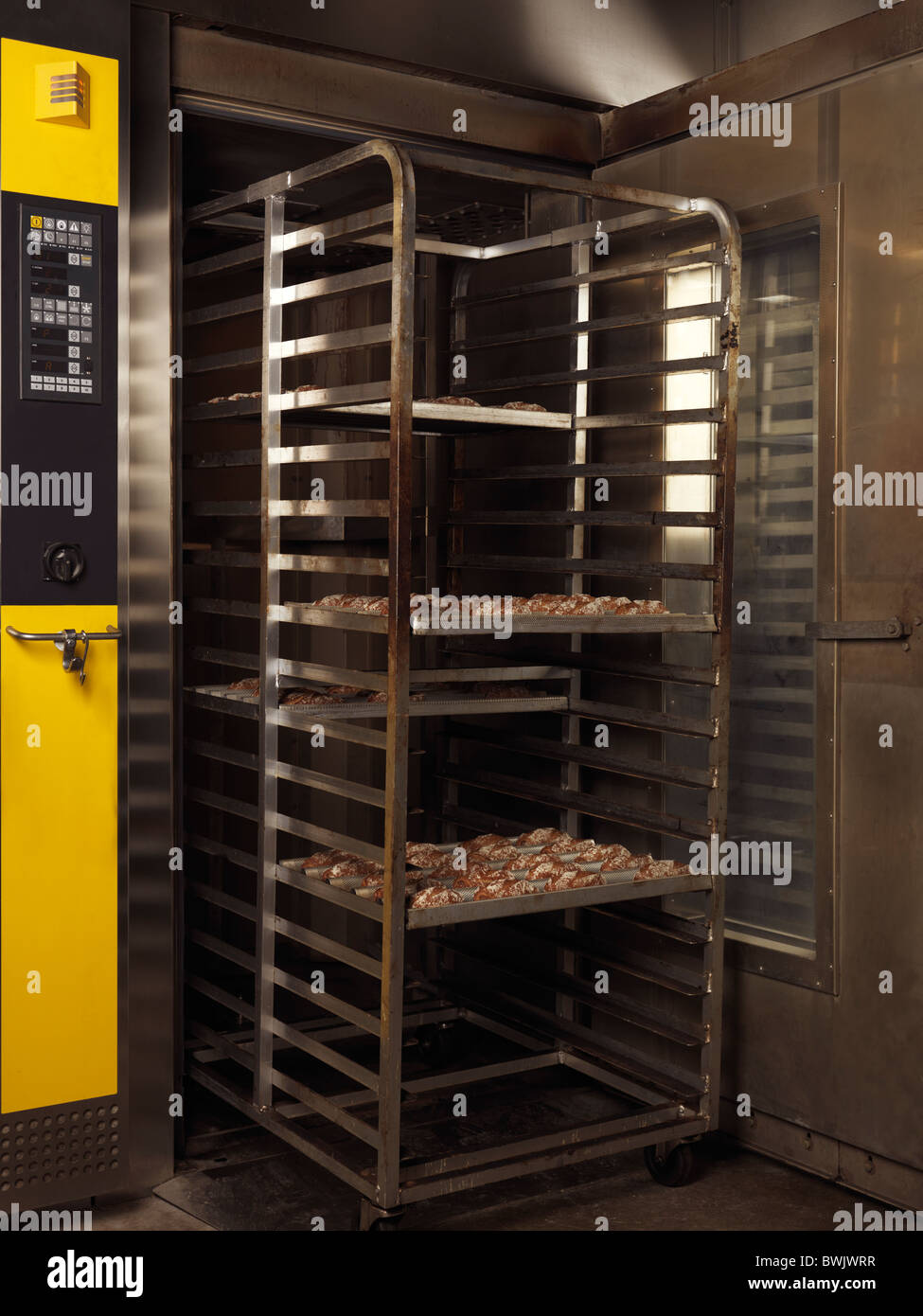 Rack trolley with freshly baked buns in a bakery oven - Stock Image