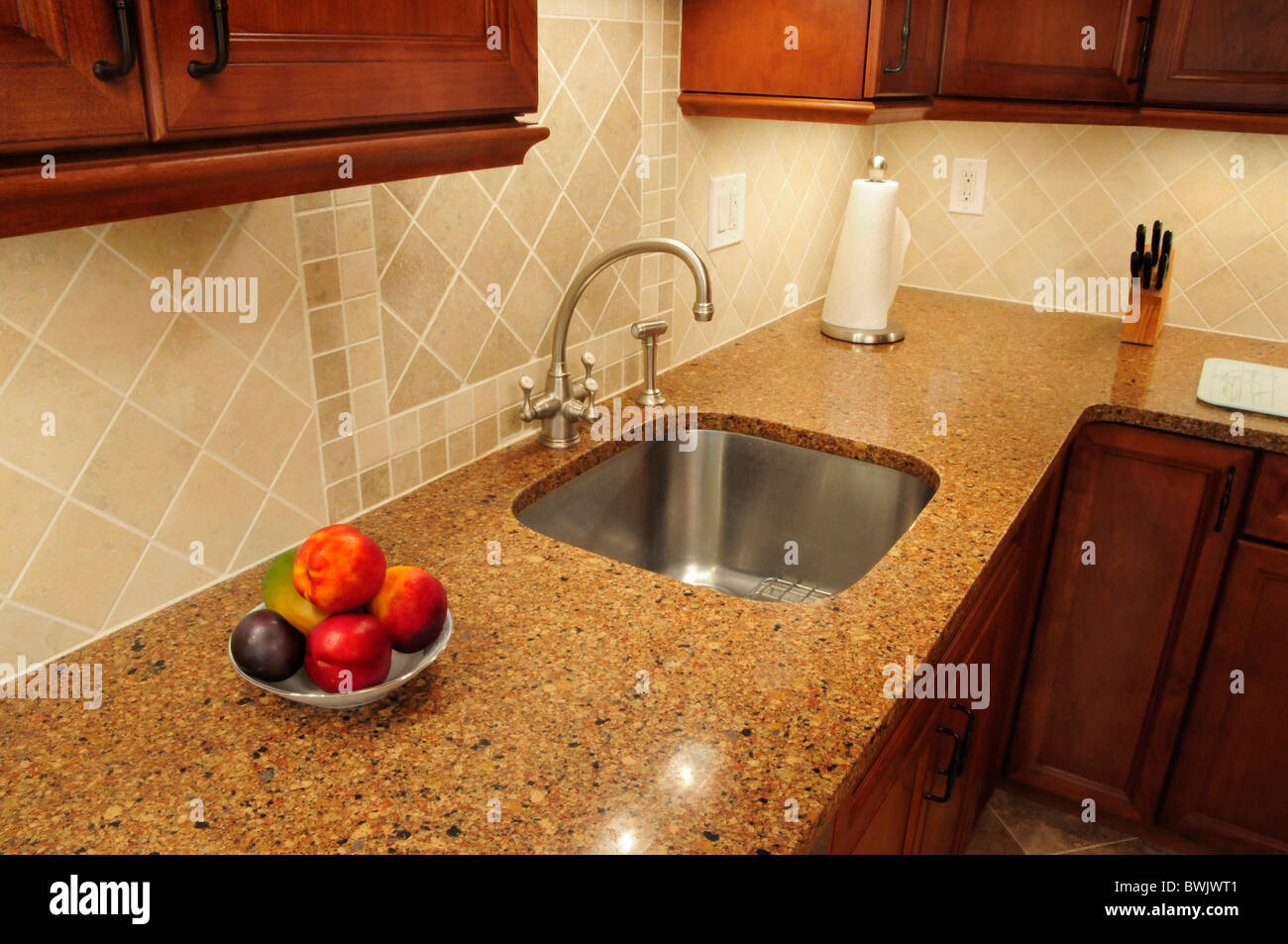 Stainless steel sink in a remodeled kitchen with a quartz counter - Stock Image
