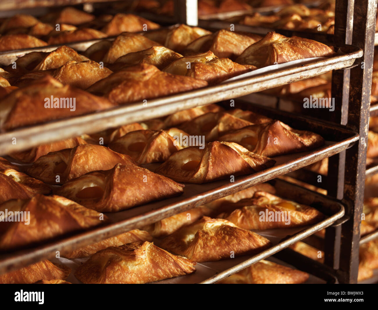 Freshly baked pastries on baking trays in bakery rack trolleys - Stock Image