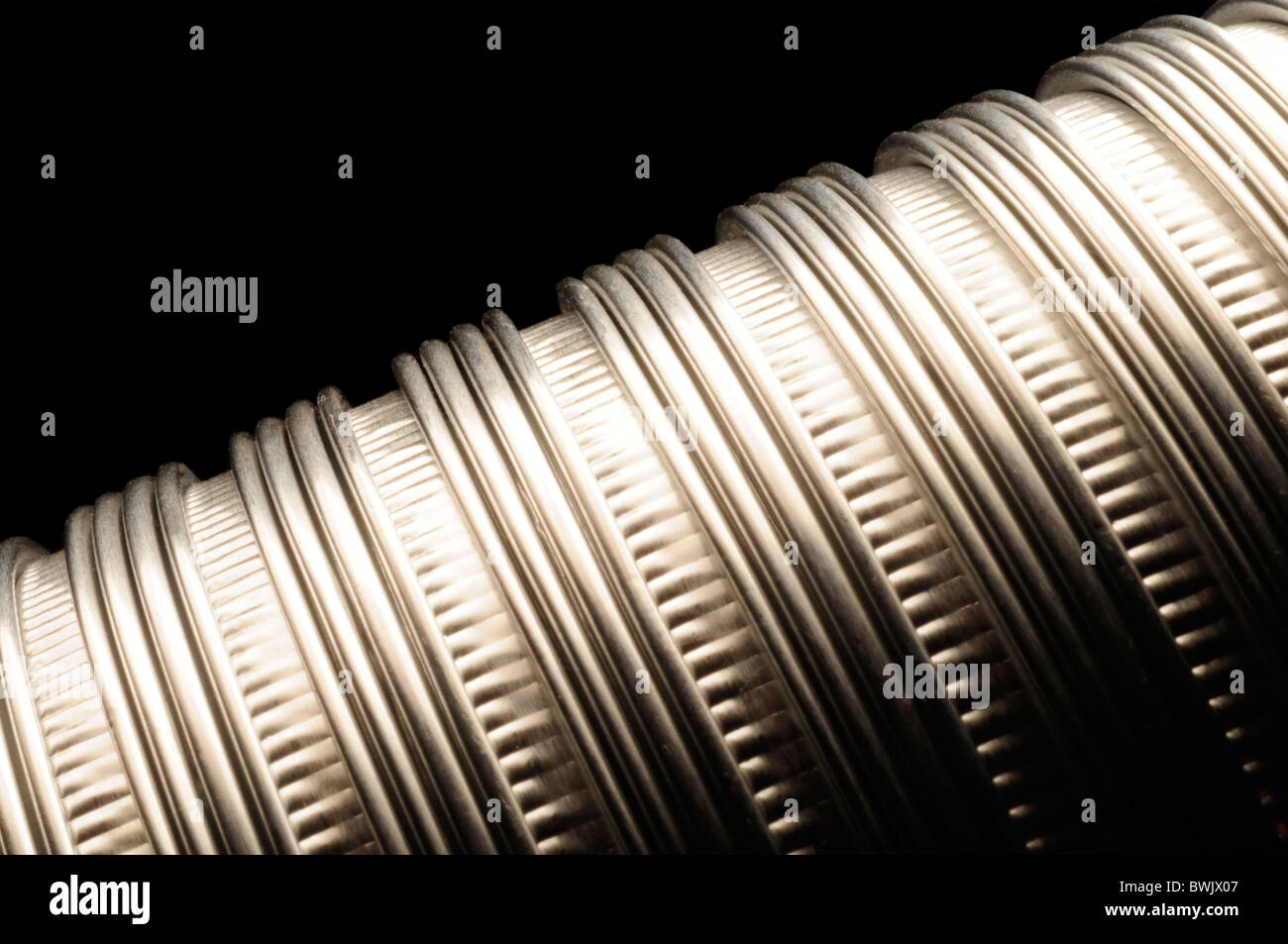 Flexible metallic aluminum vent tubing running diagonally against a black background - Stock Image