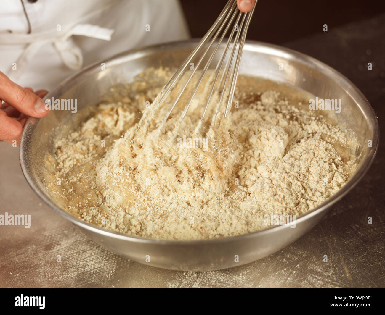 Closeup of baker's hands whisking batter with spelt flour in a bowl Stock Photo