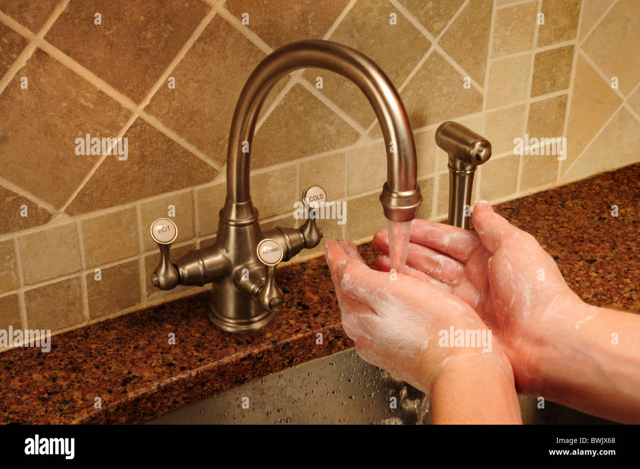 Soapy hand washing under flowing water out of a kitchen faucet - Stock Image