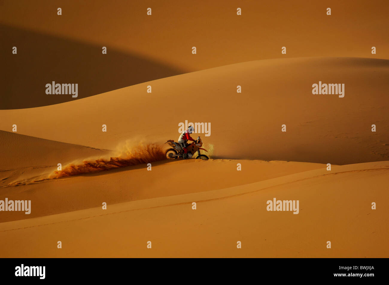 Offroad motorcycle motorbike motorcyclist adventure erg Chebbi desert sand dunes sand desert Merzouga Morocco North - Stock Image