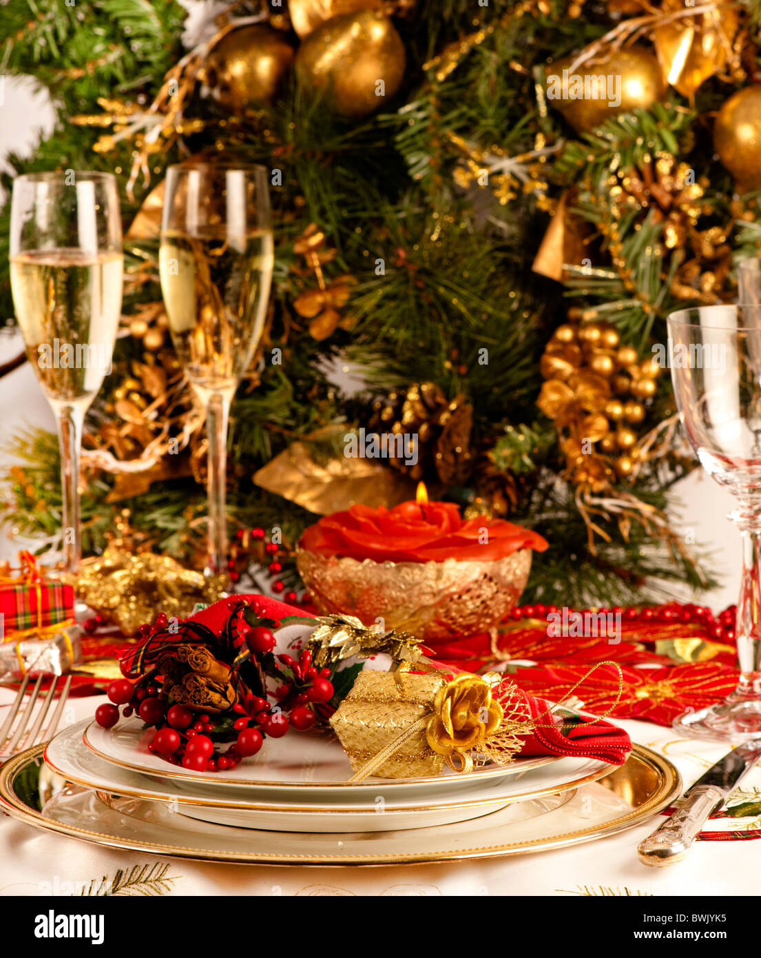 Christmas table setting with wine glass and two glasses of ch&agne Red and gold decorations and presents. & Christmas table setting with wine glass and two glasses of champagne ...