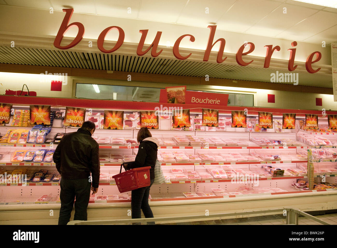 Buying meat at the meat counter in a French supermarket, Meaux, Ile de France Northern France - Stock Image