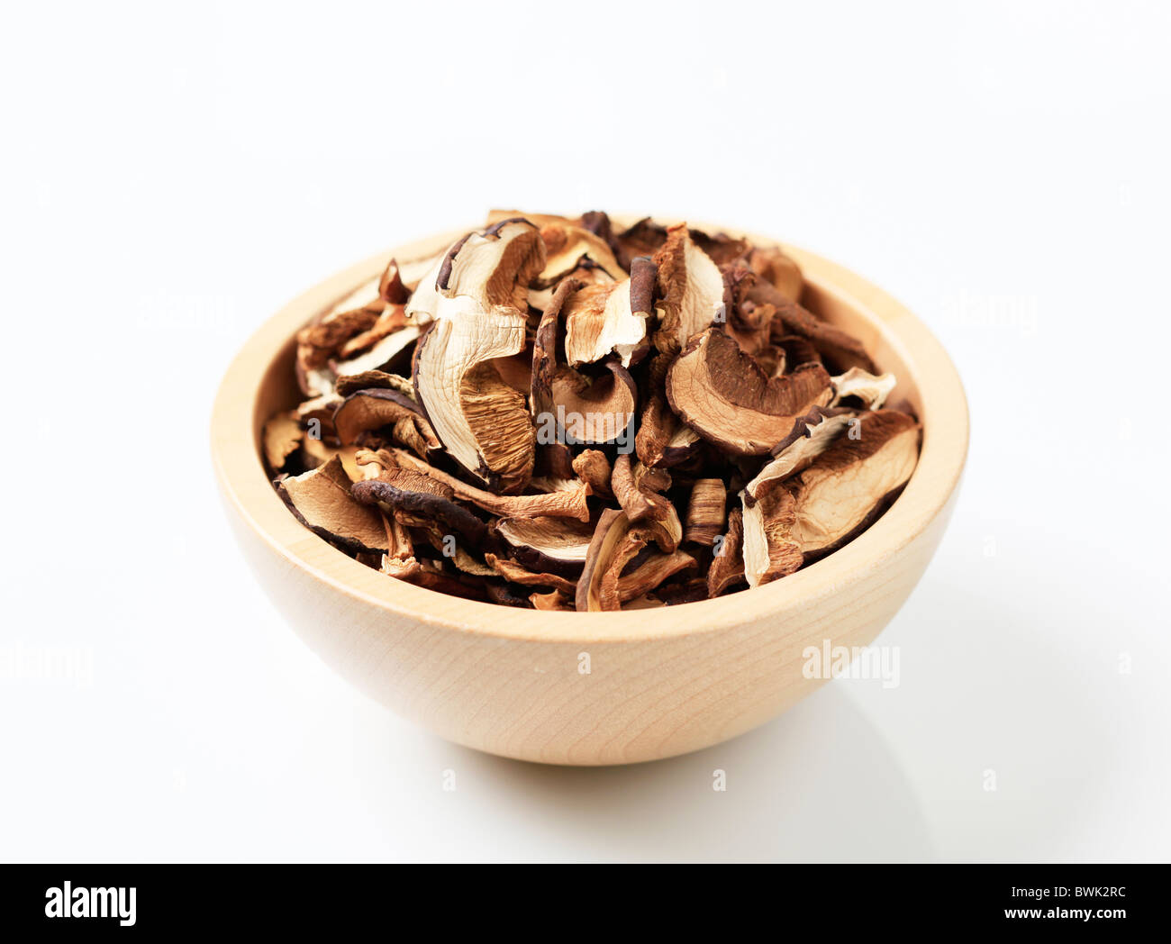 Dried mushrooms in a wooden bowl - Stock Image