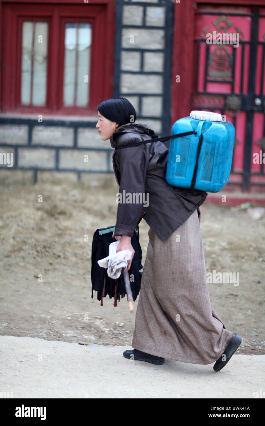 A local lady carrying water in Litang, Sichuan province, southwest China - Stock Image