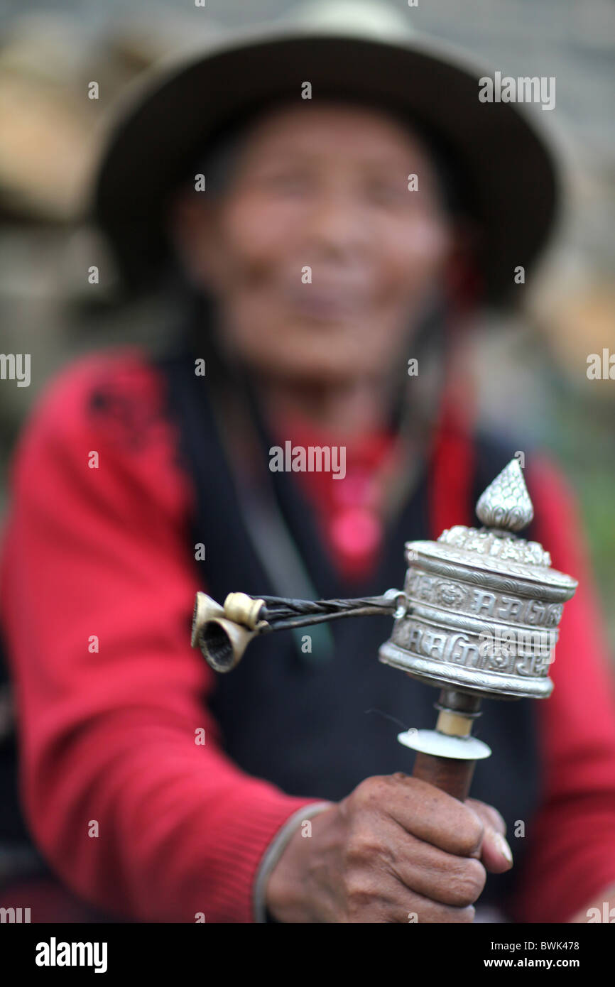 A tibetan woman spinning a prayer wheel in Litang, Sichuan province, southwest China. - Stock Image
