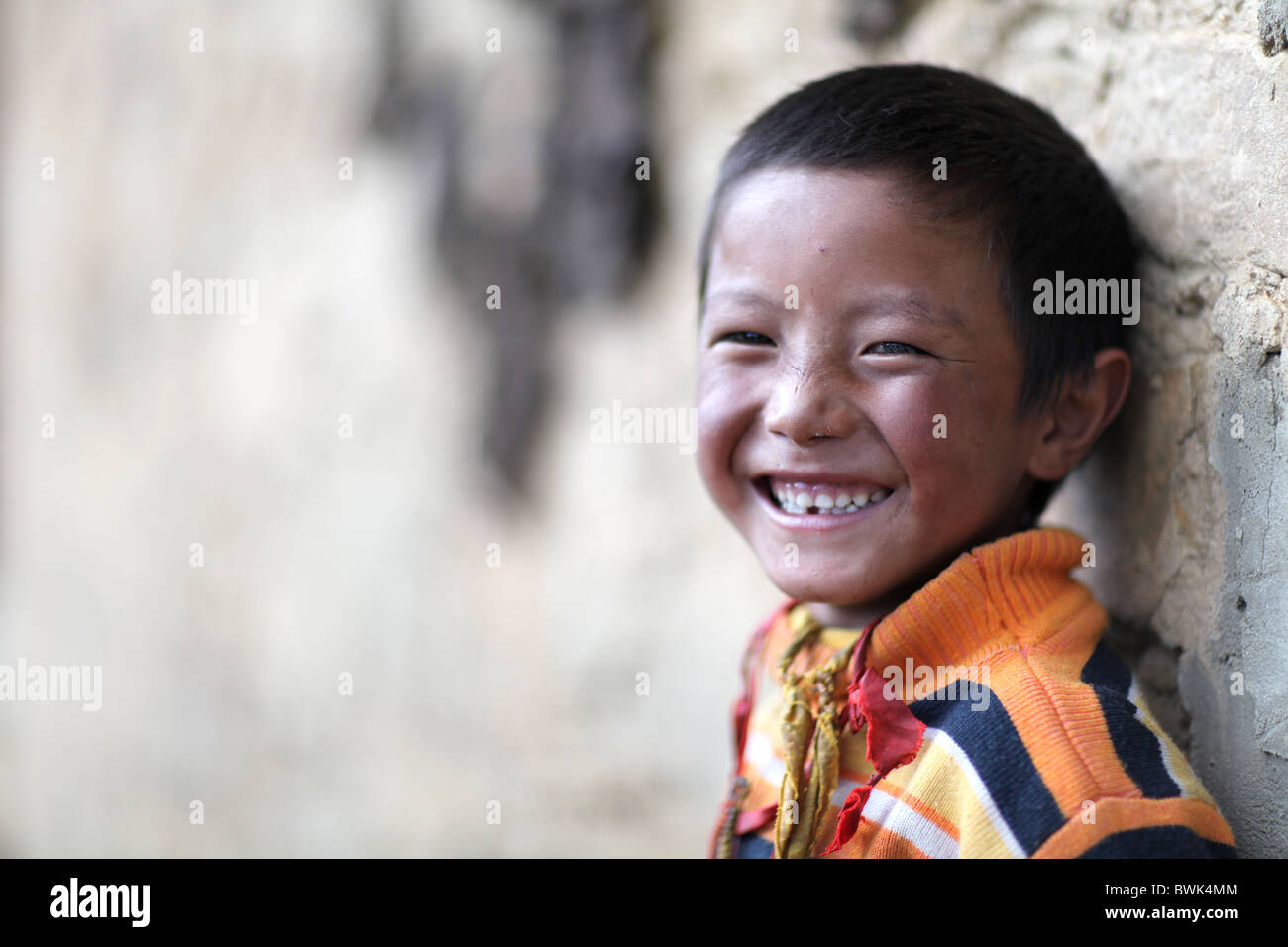 A young tibetan smiling boy in Litang, Sichuan province, southwest China - Stock Image
