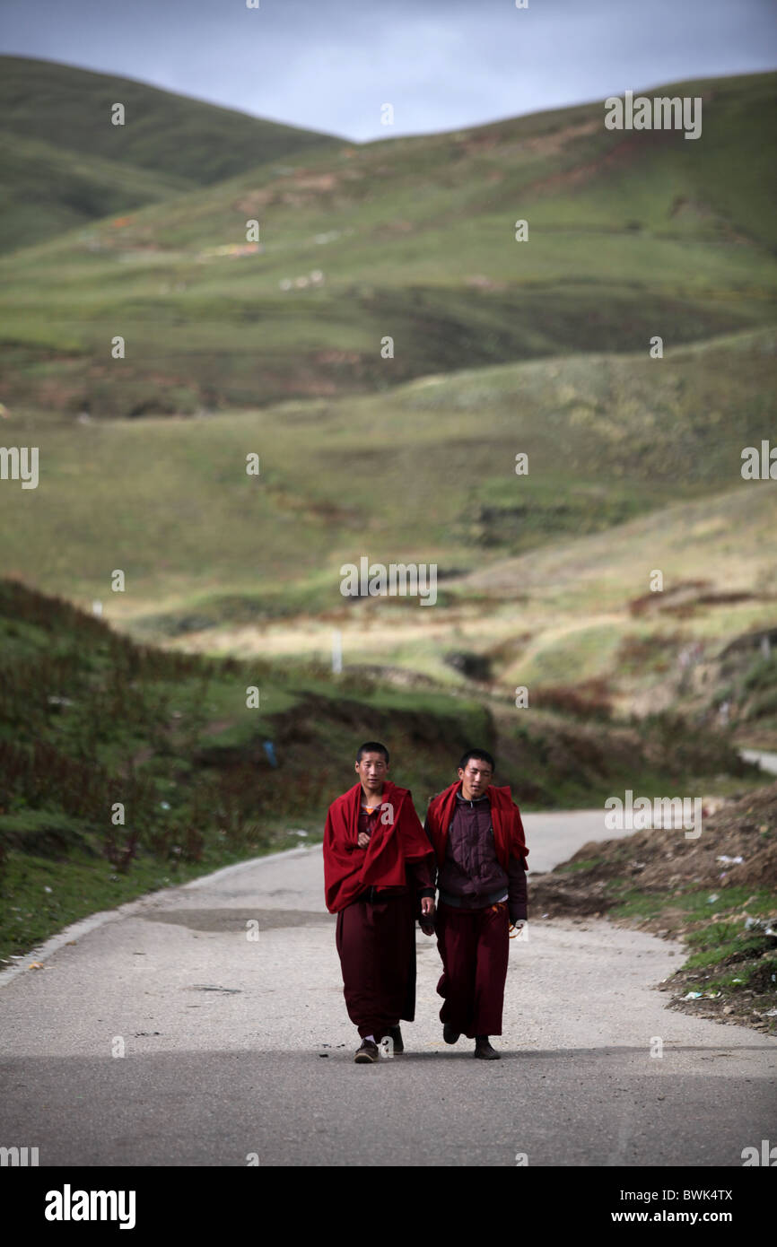 Two monks walking in the hills around Litang, Sichuan province, southwest China - Stock Image