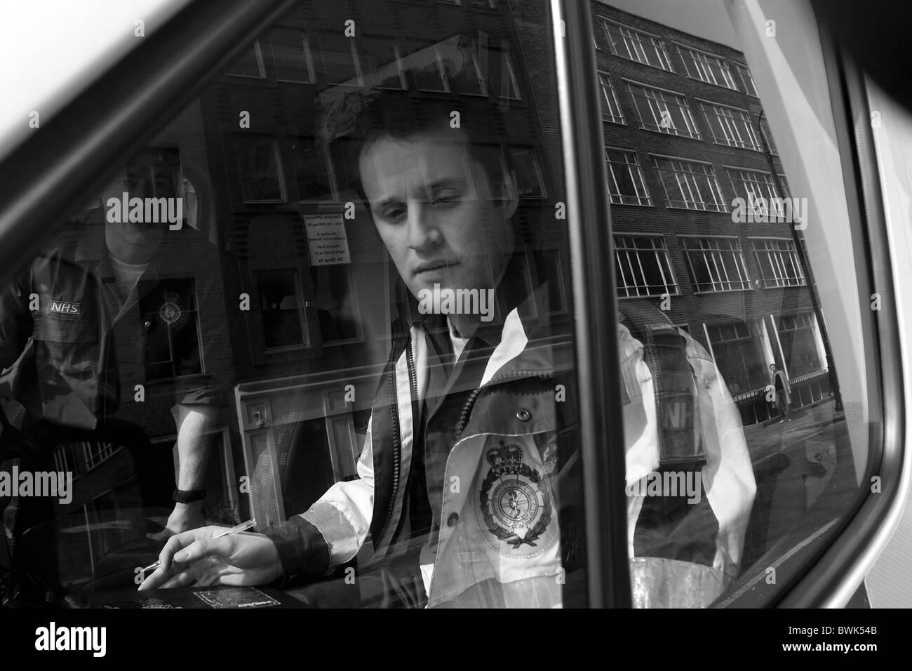 United Kingdom, London Ambulance Service.  A paramedic looks out of the ambulance window. - Stock Image