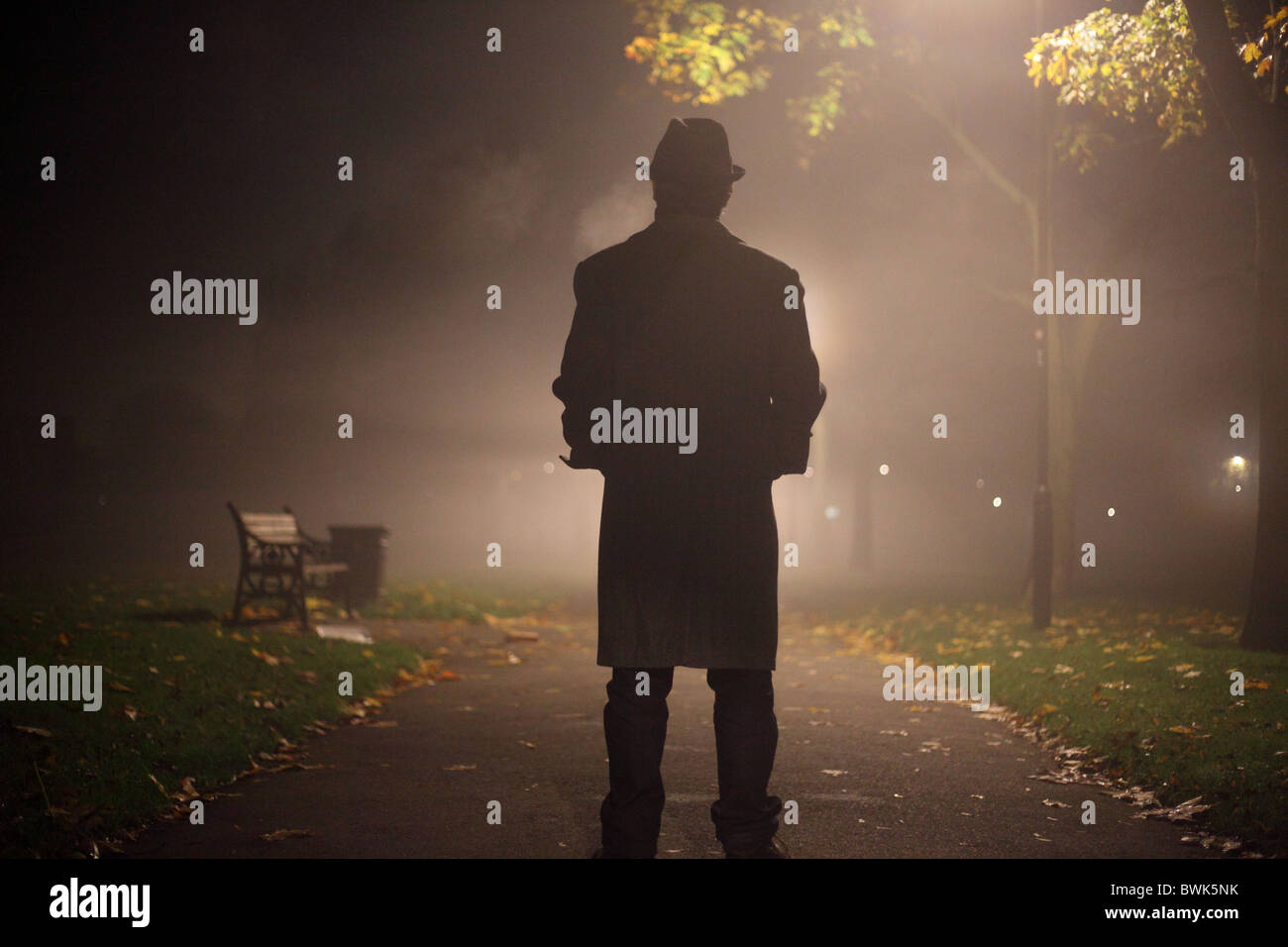 man with trench coat and hat in the park - Stock Image