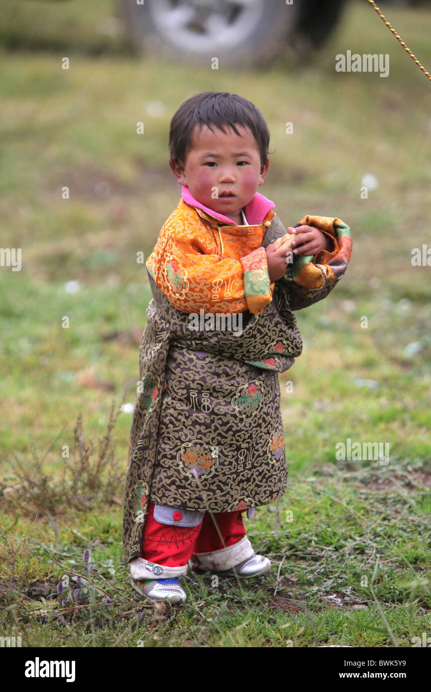 Traditionally dressed child at a local festival in the countryside near Litang, Sichuan province, southwest China - Stock Image