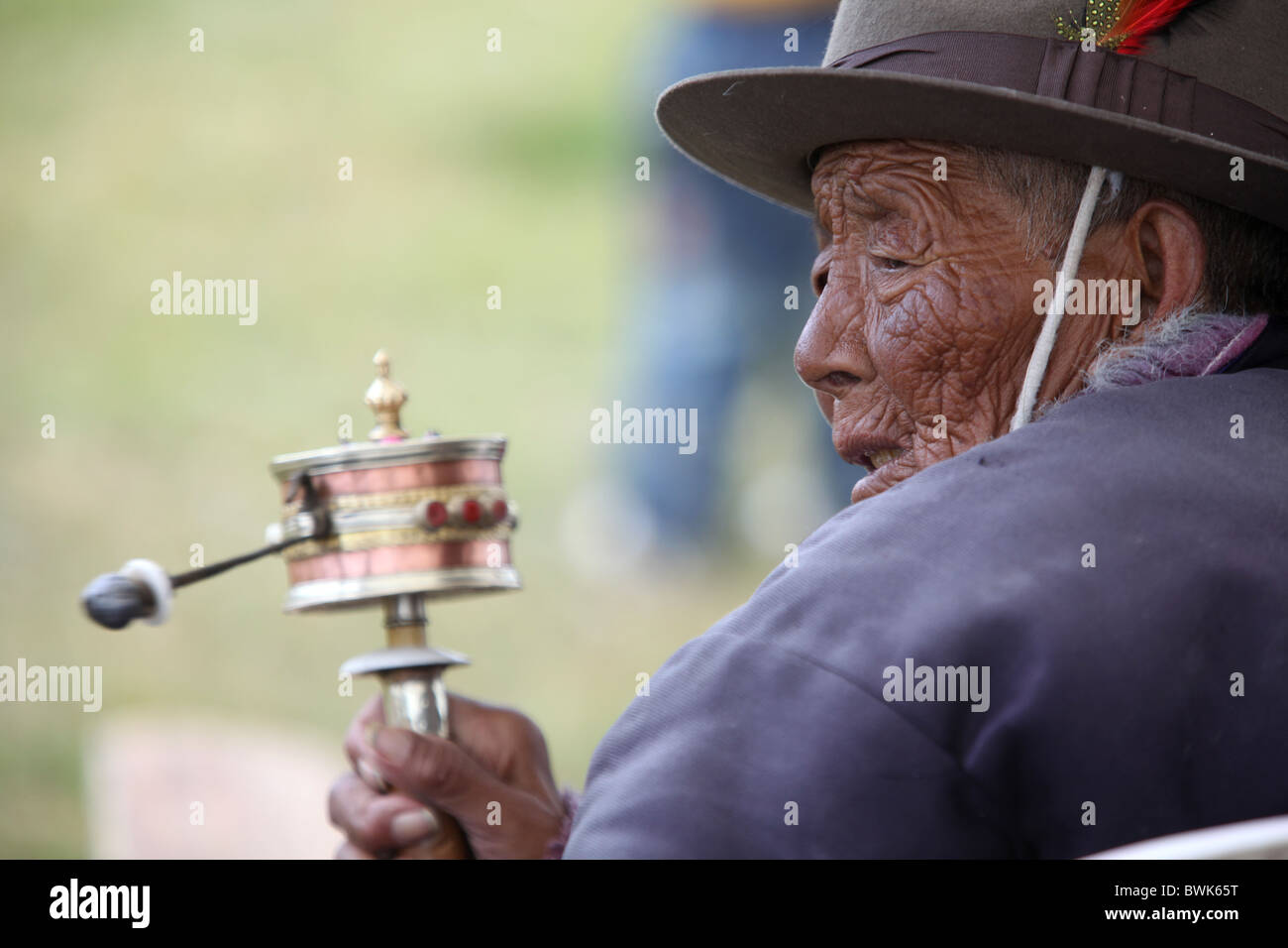 A local man spinning a prayer wheel in Litang, Sichuan province, southwest China. - Stock Image