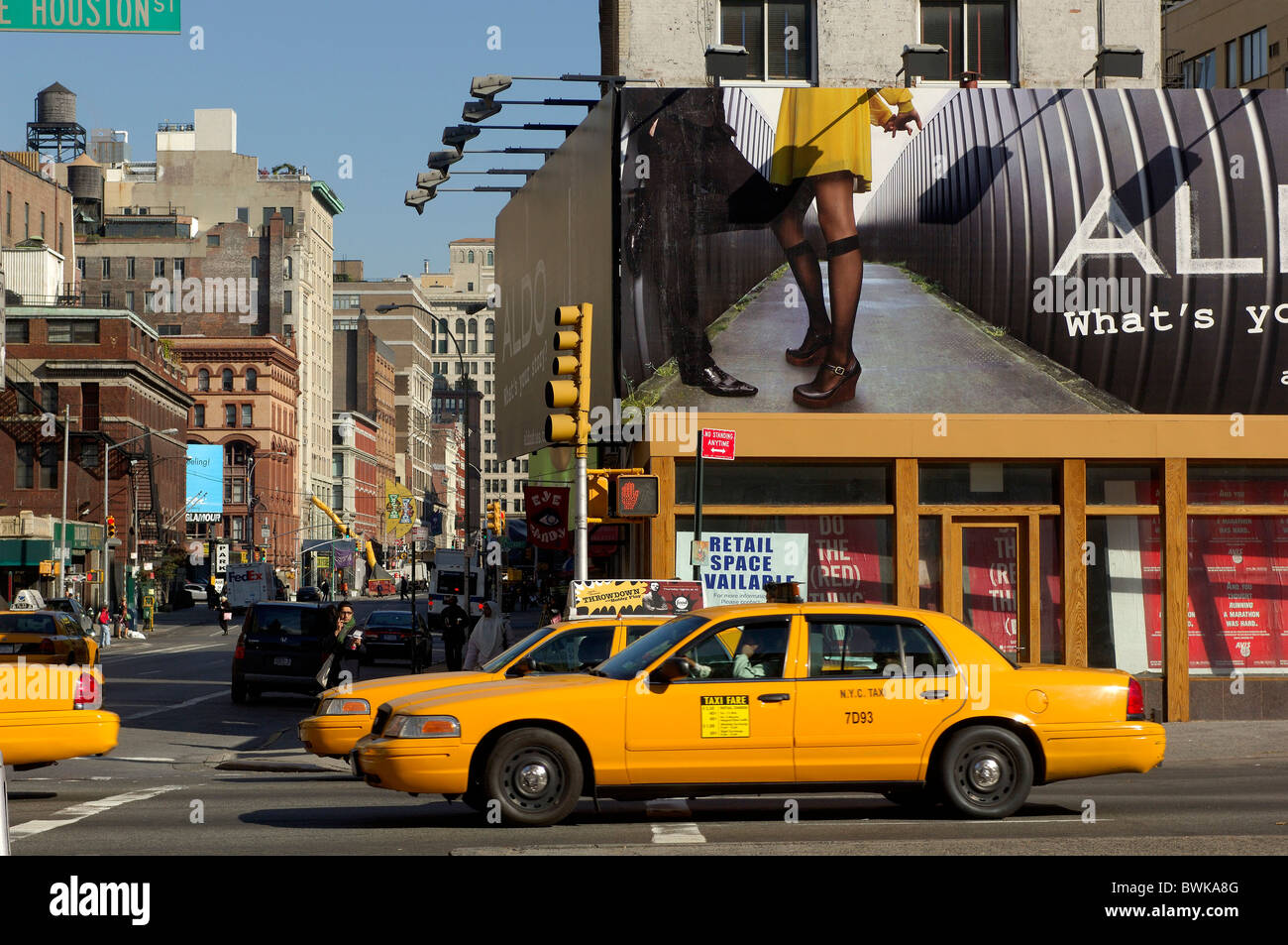 posters advertisements advertising taxi Yellow cabs street scene outside street crossroad intersection Houst - Stock Image