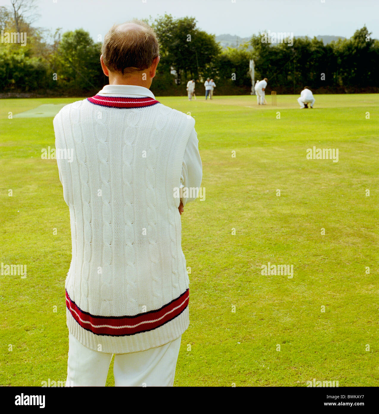 Man fielding in cricket match, in white sports outfit - Stock Image