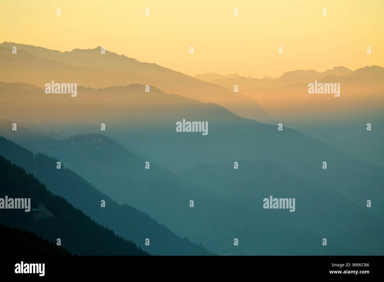 mountain landscape silhouettes outlines fogs smoke mood dusk twilight Alps mountains scenery landscape Dis - Stock Image