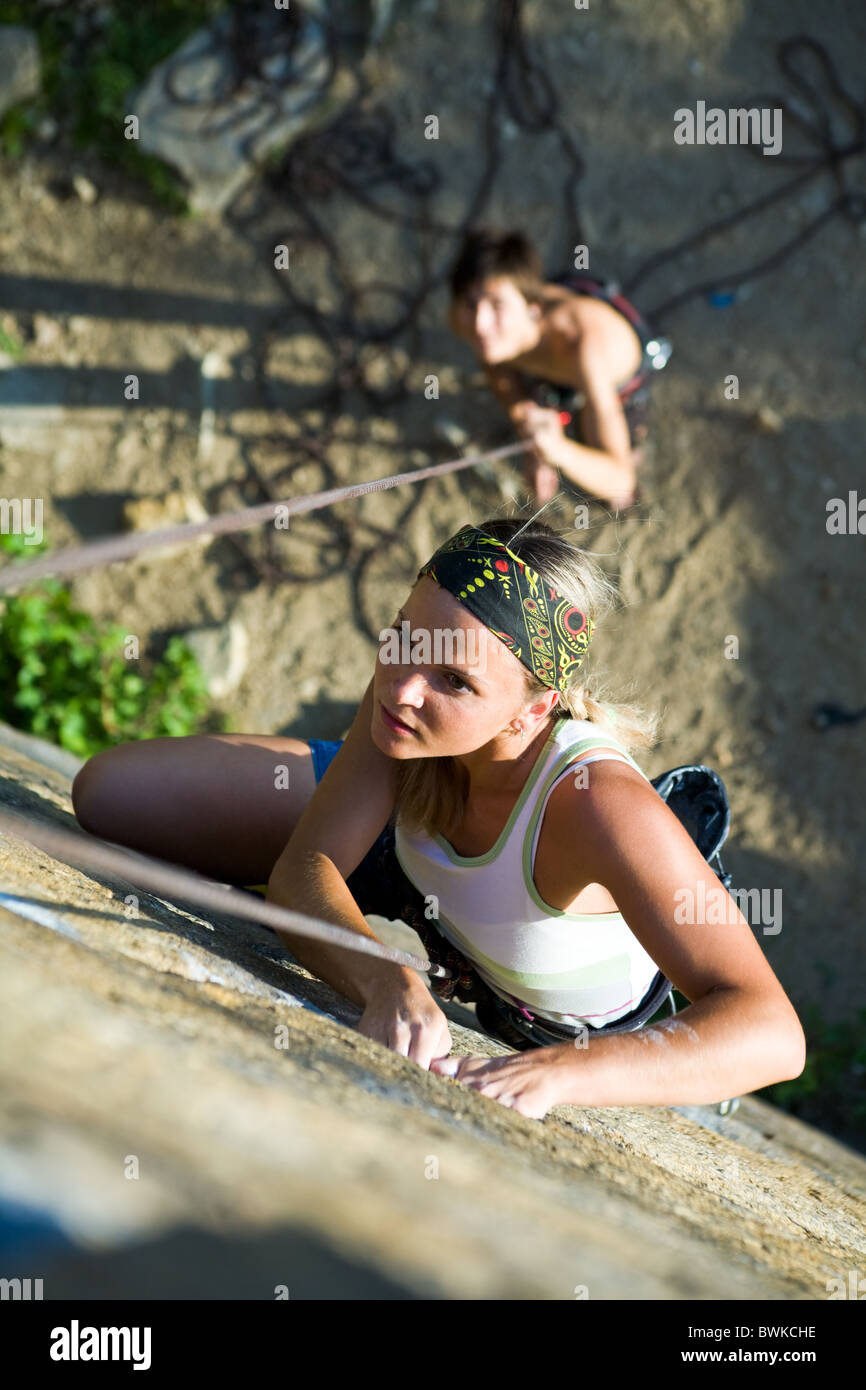 Photo of woman climbing on the rock and man standing by her - Stock Image