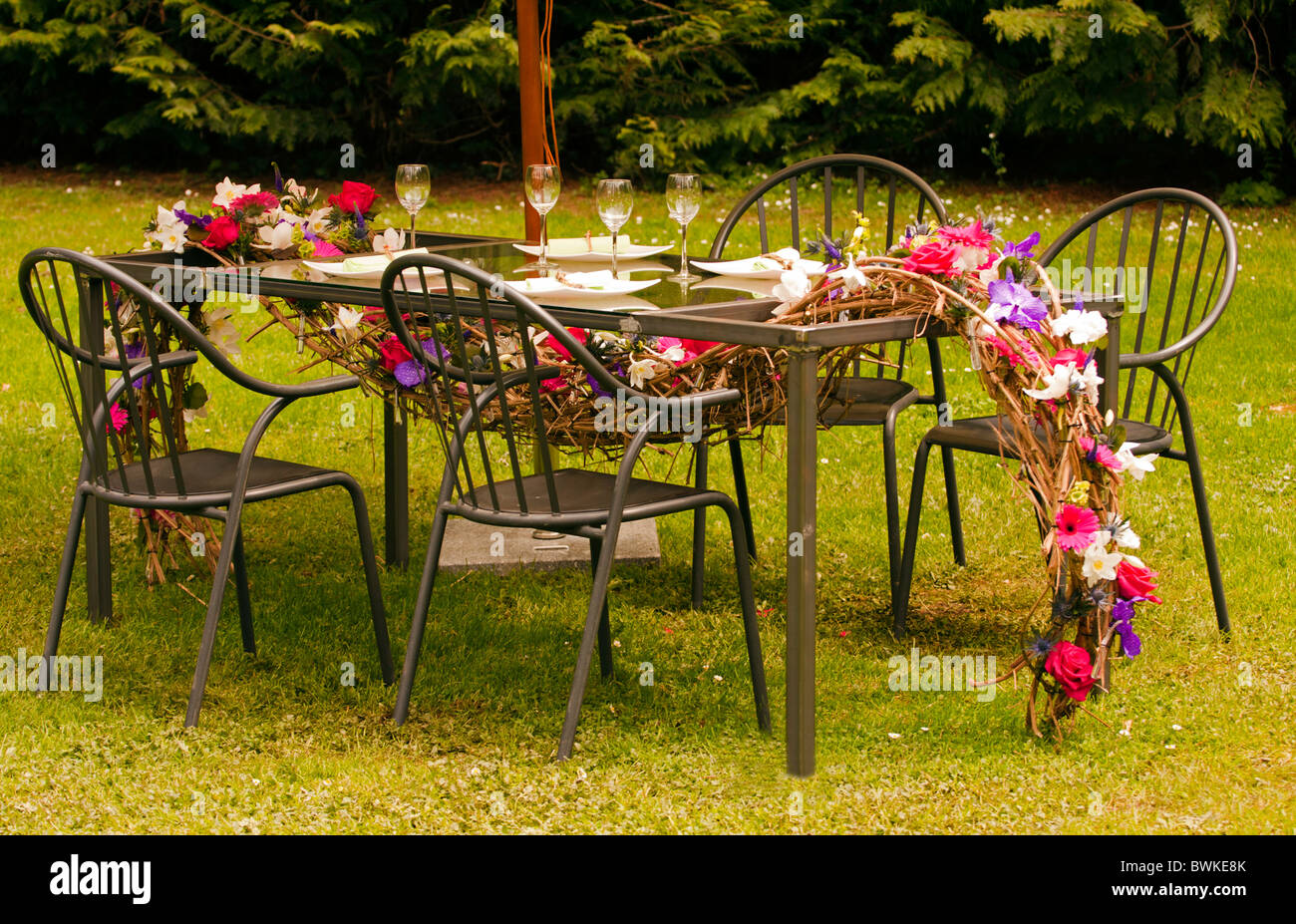 Table and chairs setup outside in the garden. - Stock Image