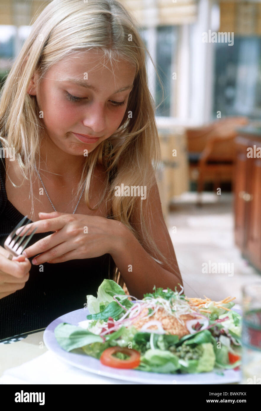 Preteen child turn down live food salad in restaurant - Stock Image