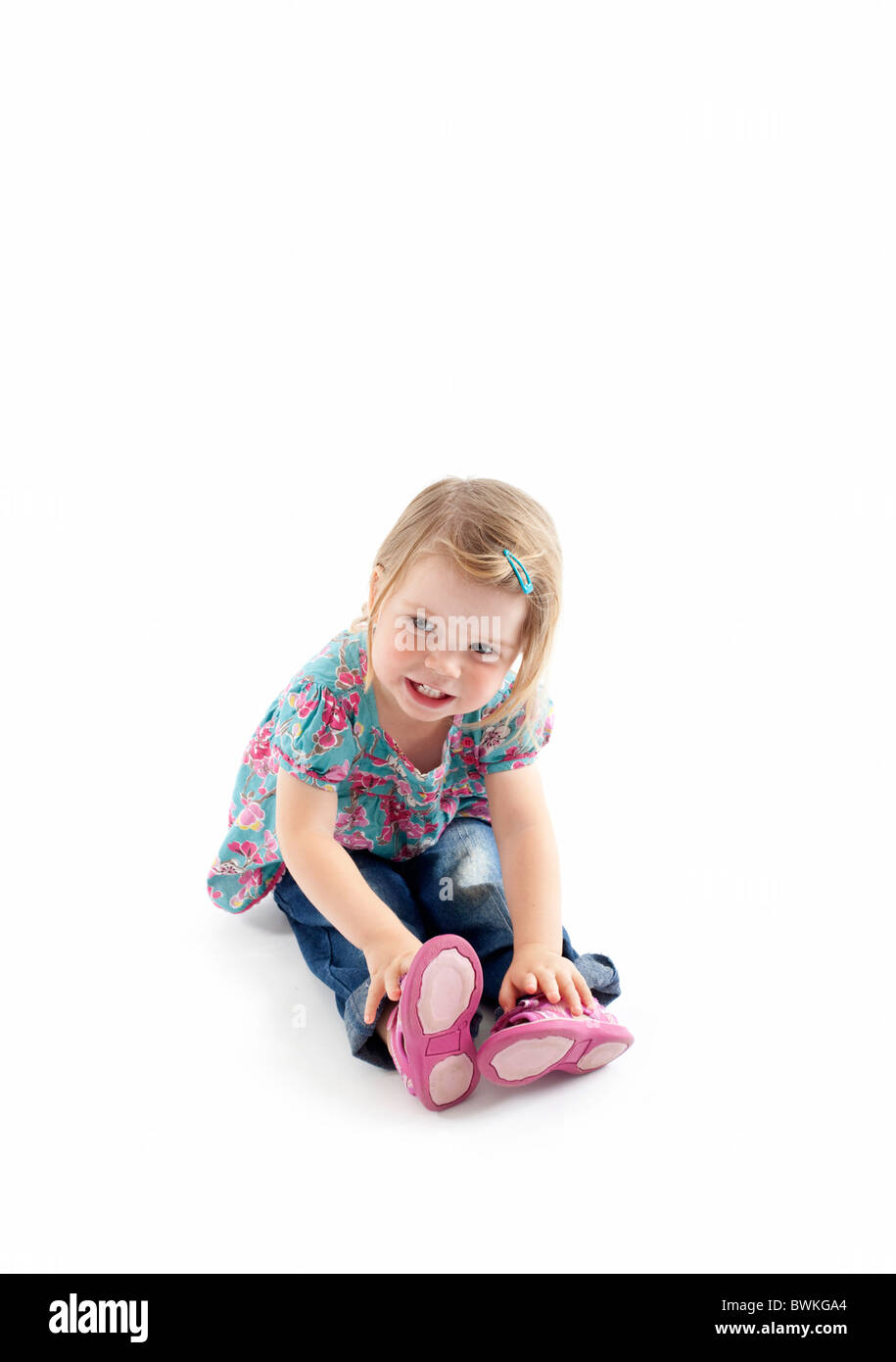 toddler sitting on floor with isolated white background Stock Photo