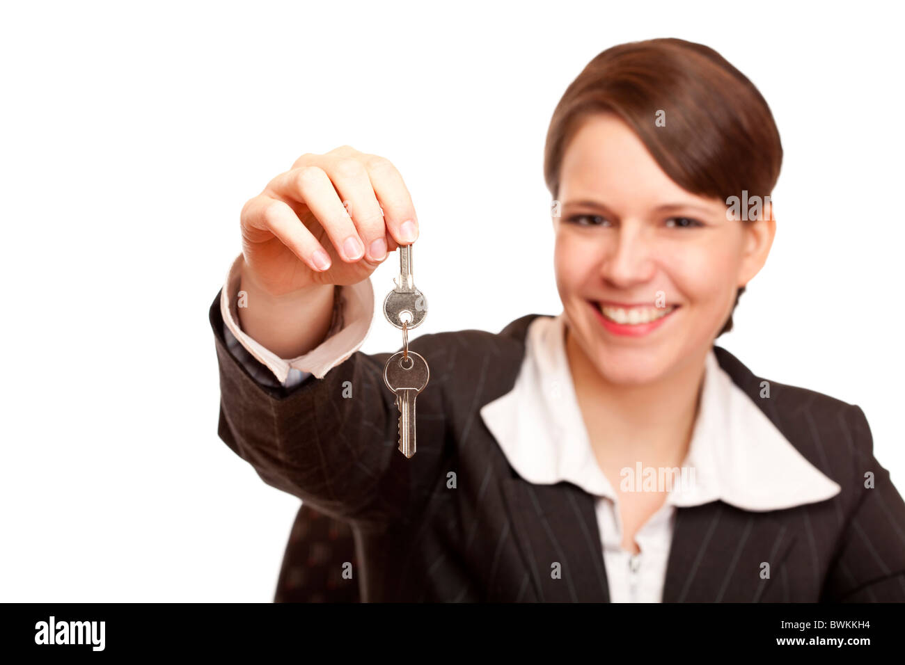 Smiling woman gives over house key. Isolated on white background. - Stock Image