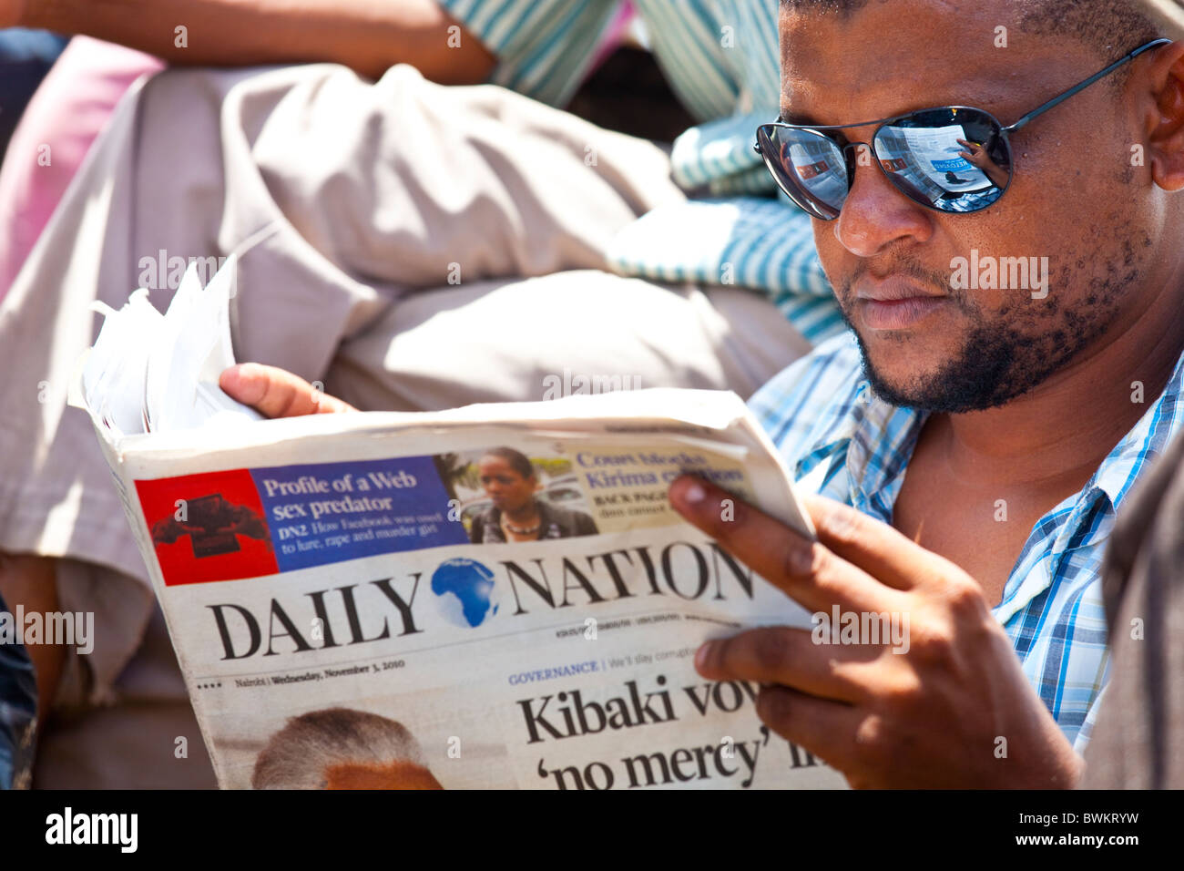 Man reading the Daily Nation newspaper, Nairobi, Kenya - Stock Image