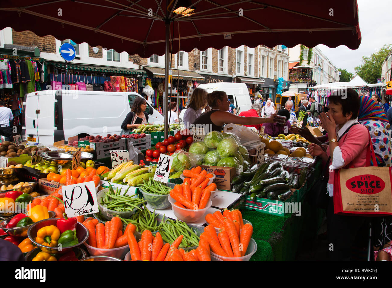 Selection of fresh fruits and vegetables at at fruits and vegetable stall at Portobello Road market with customers - Stock Image