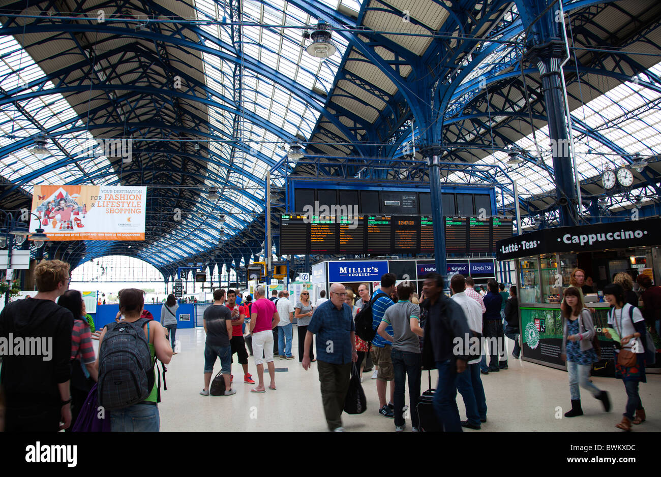 Travellers commuters at Brighton Railway Station on a summer day with view of Arrivals and Departures on screen Stock Photo